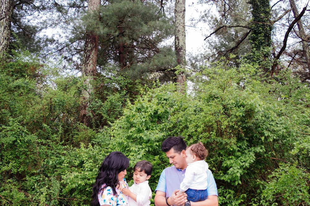 man and woman carrying kids standing beside green plants during daytime