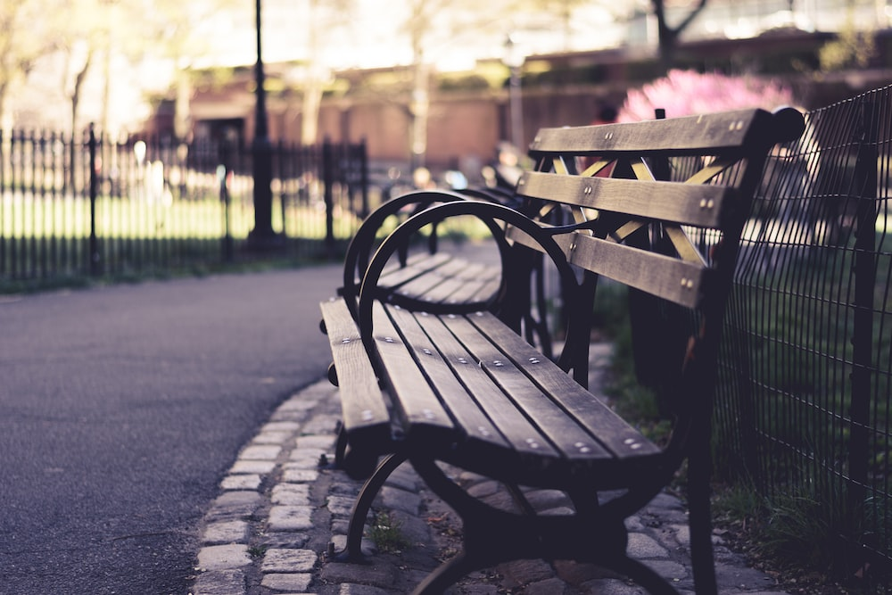 brown wooden bench beside black fence
