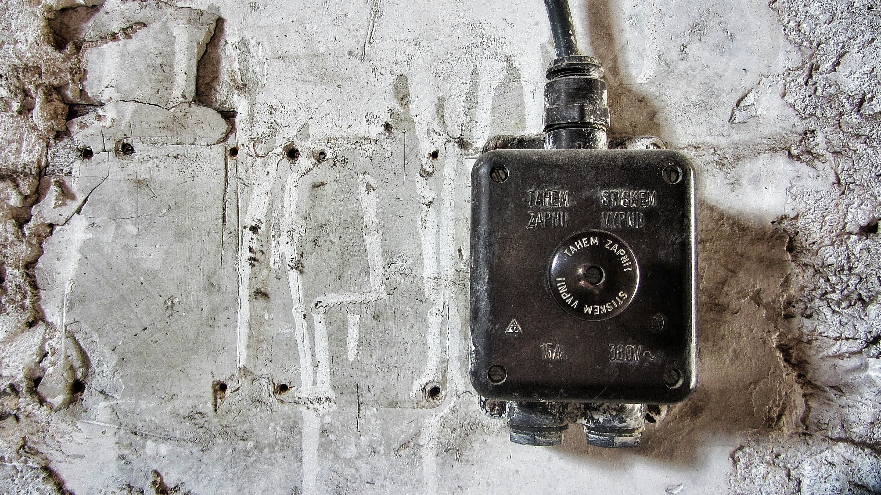 Old black electric box situated on a gray concrete wall