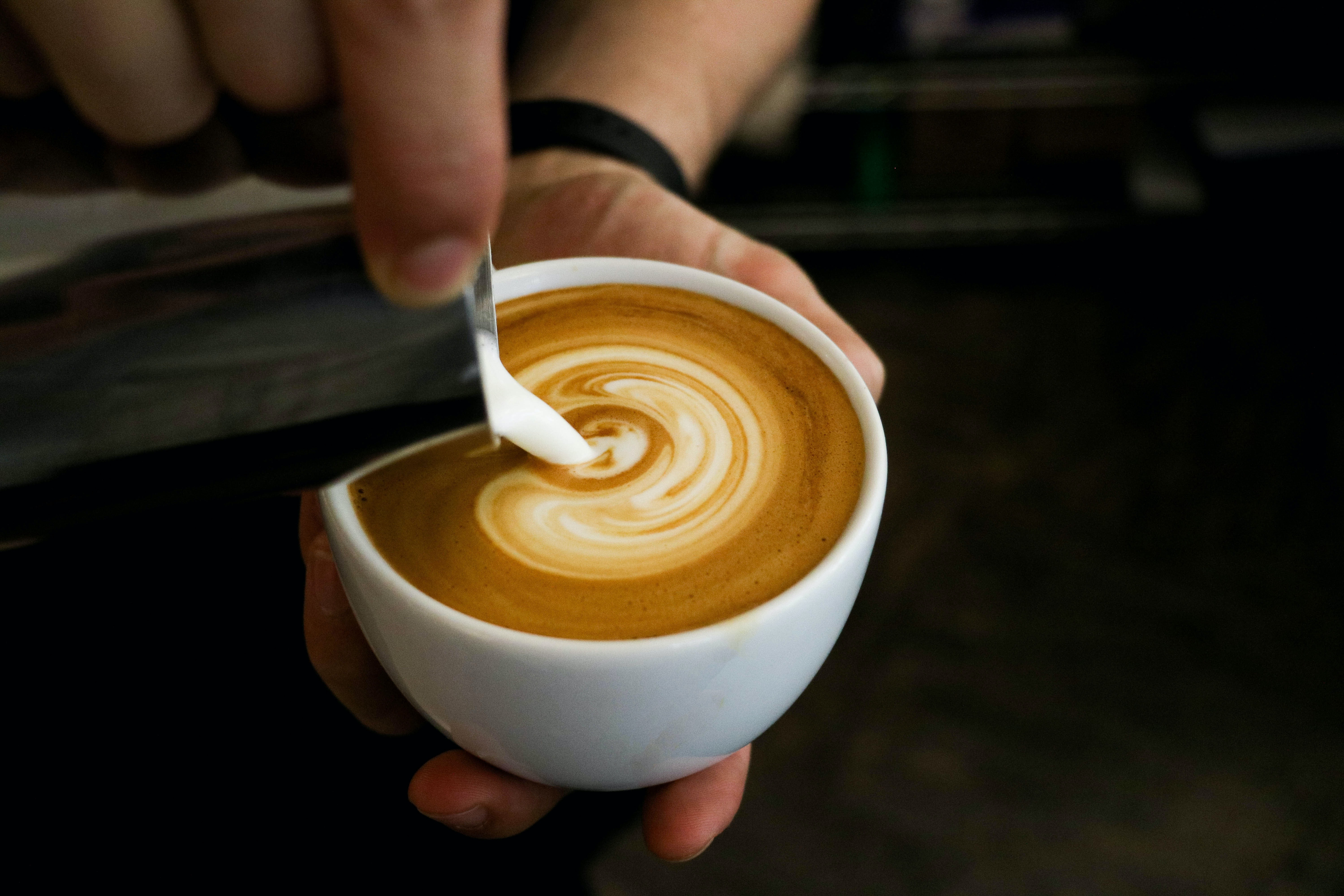 A person's hands holding a coffee cup and pouring cream into it