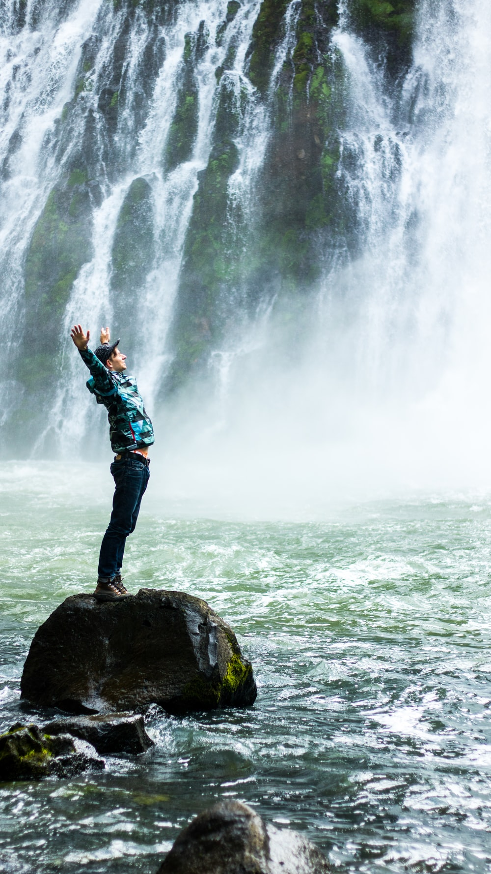 man standing on black rock surrounded body of water