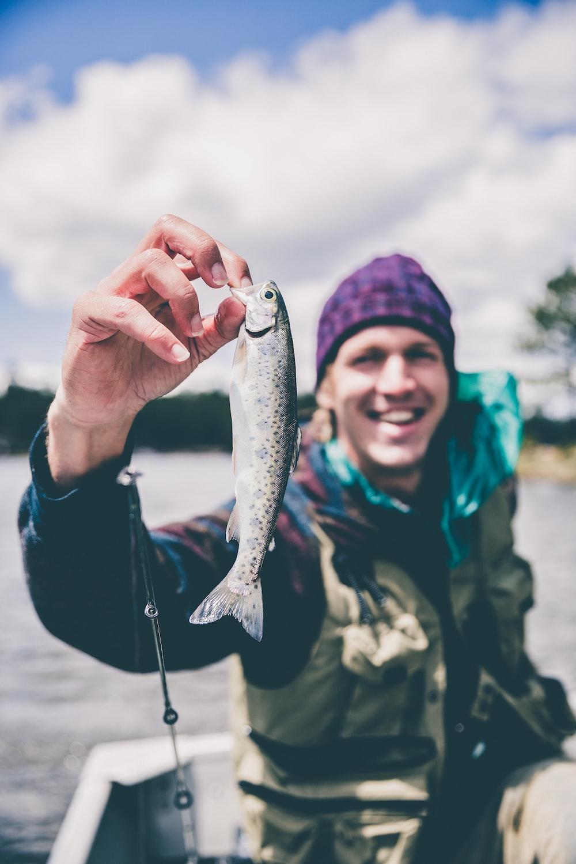 depth photography of man holding fish