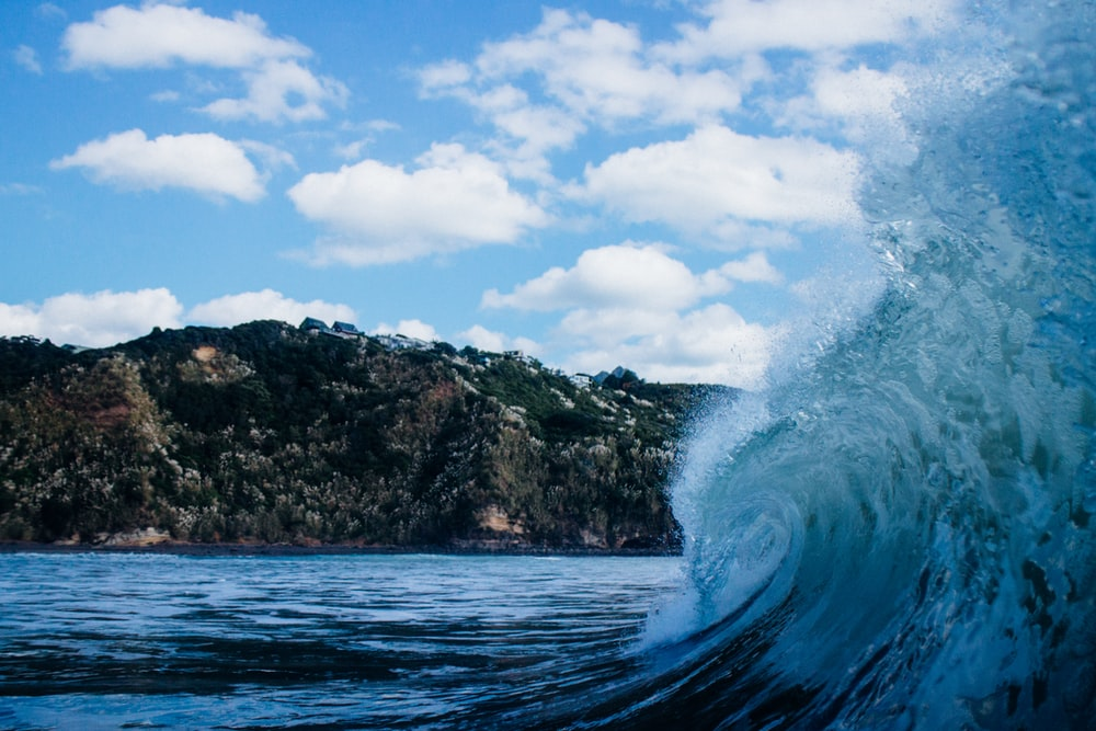 close-up photography of sea wave under white clouds and blue sky