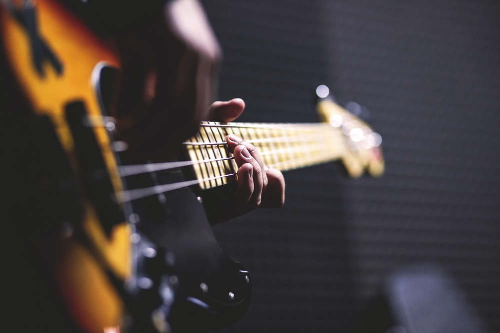 closeup photo of person playing guitar