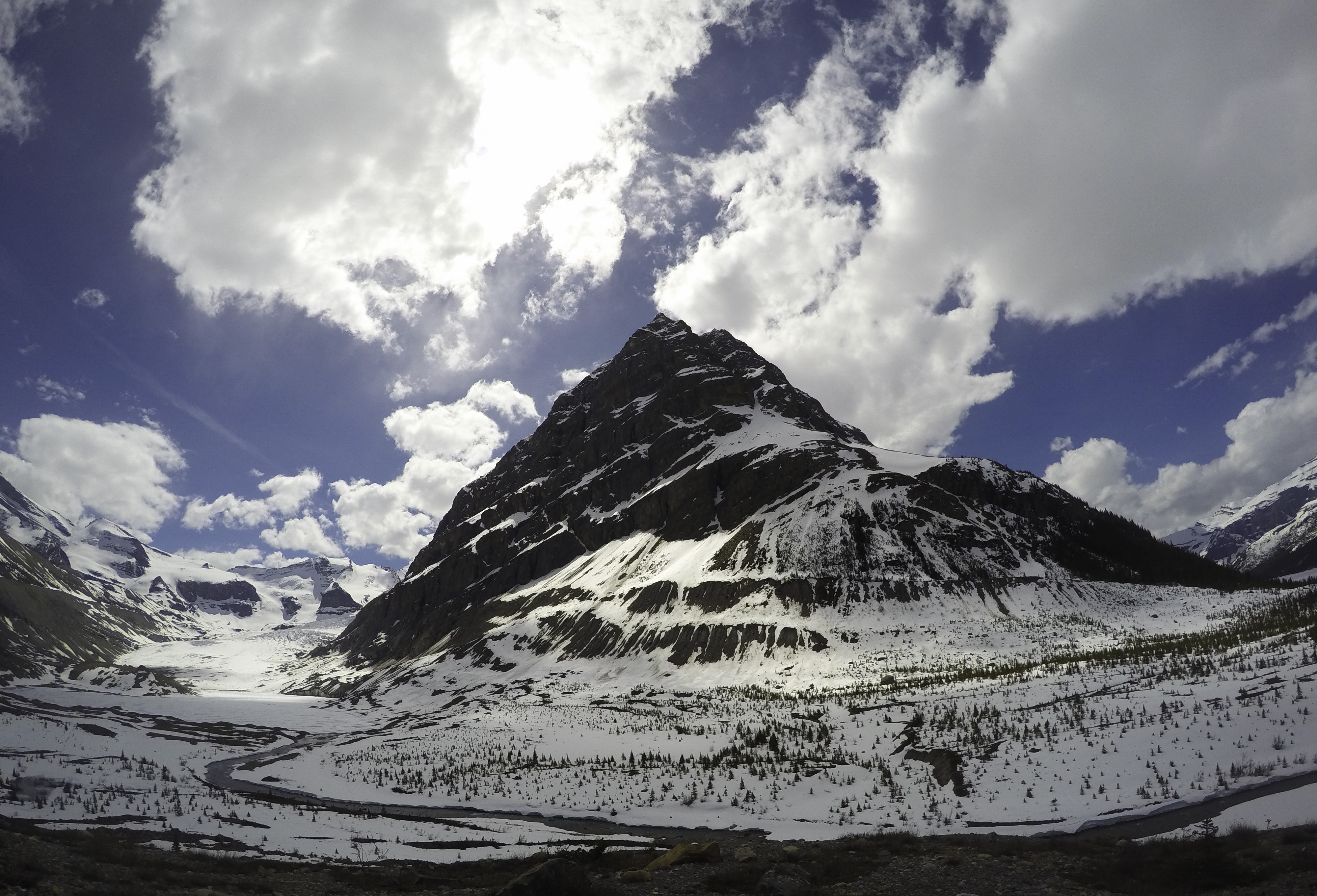 Fluffy clouds flit past the snowy rocky valley of Mount Robson