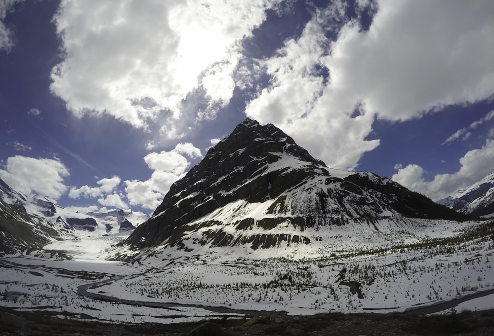 photo of rock mountain covered with snow