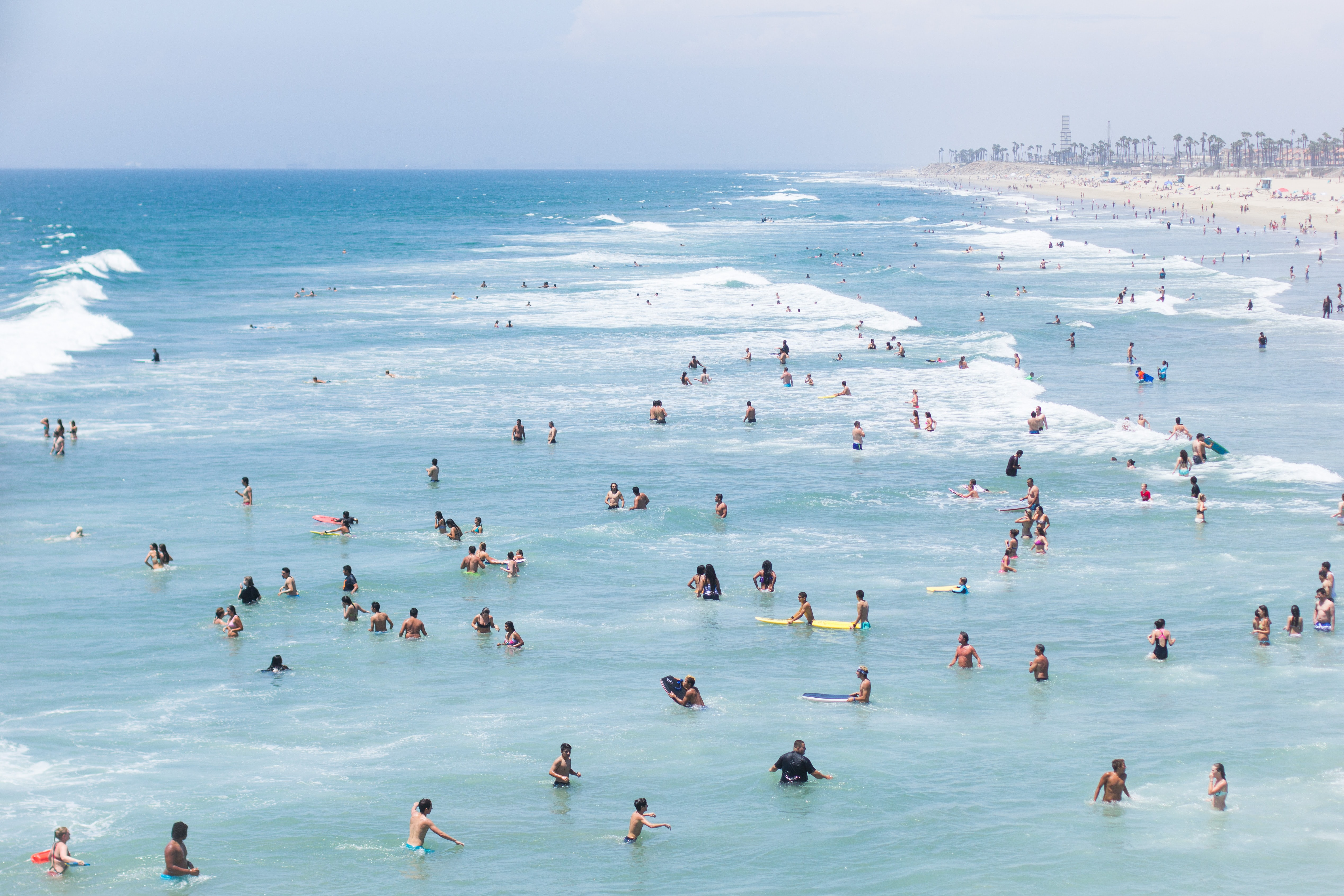 Huntington beach filled with swimmers, surfers and people on the shore