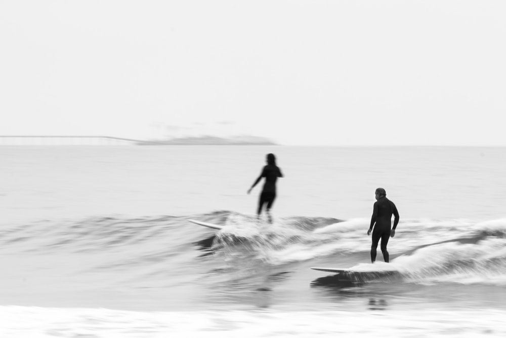 grayscale photography of two person surfing