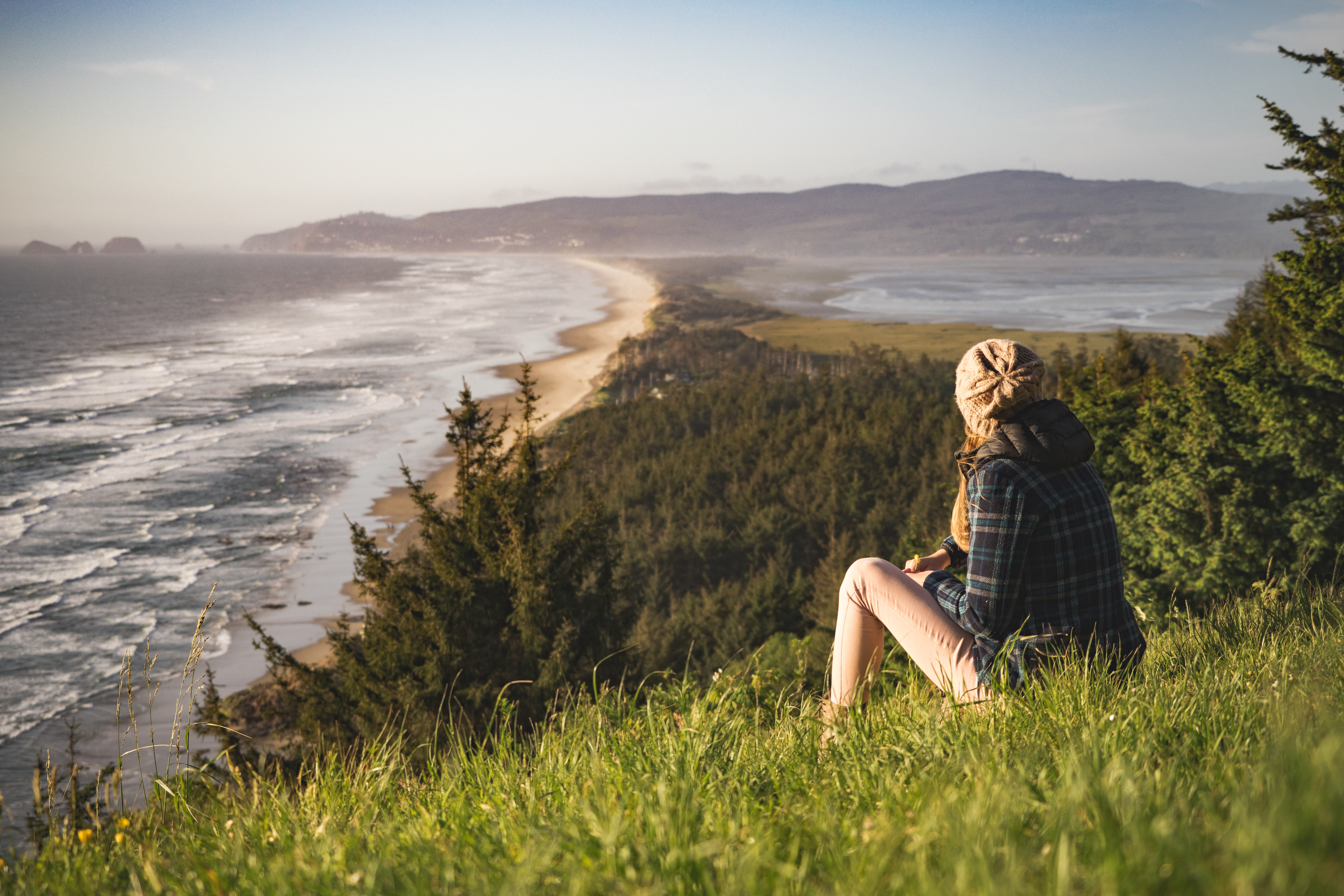 A woman in a coat and hat sitting on a grassy hill looking over the beach