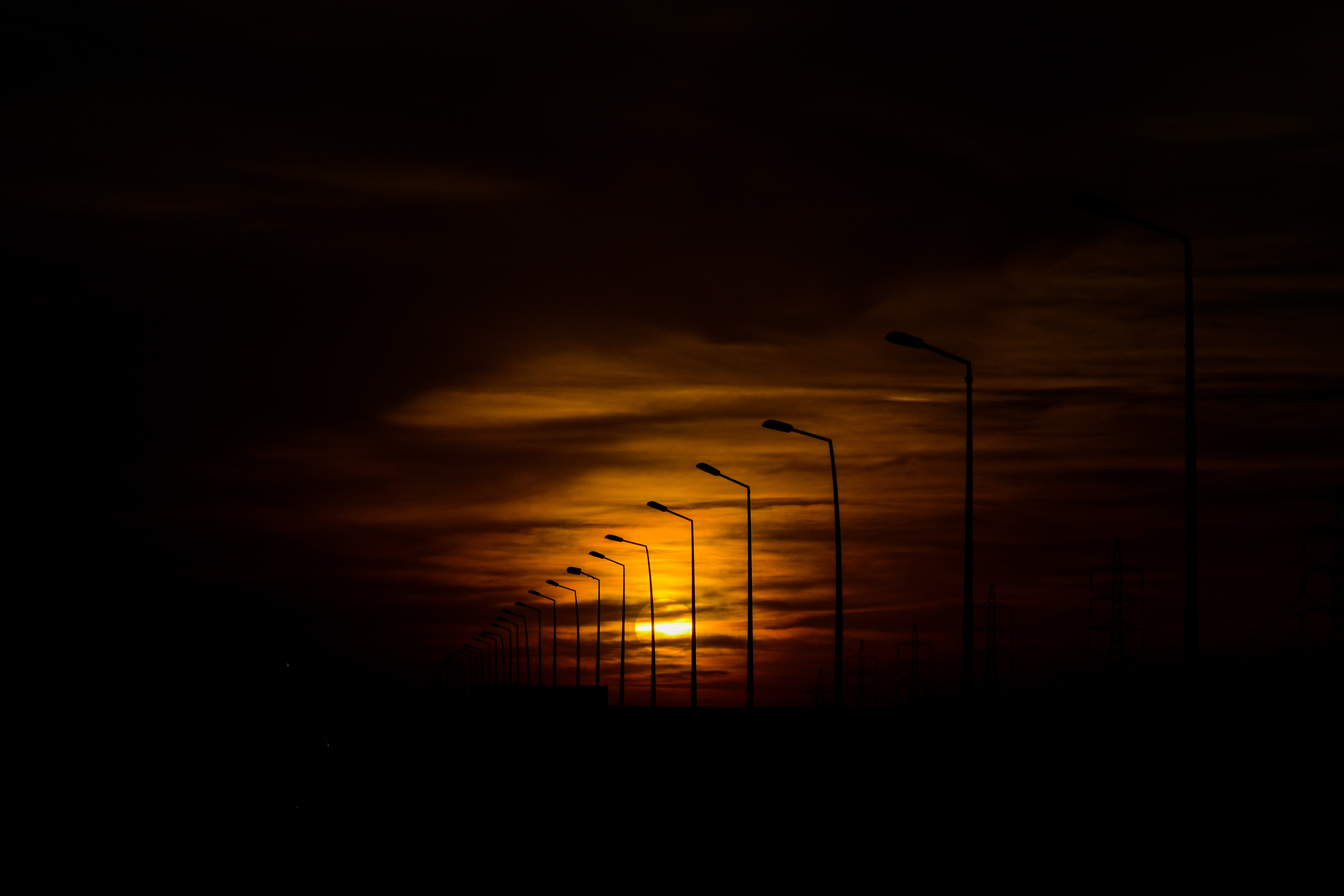 silhouette street lights during sunset