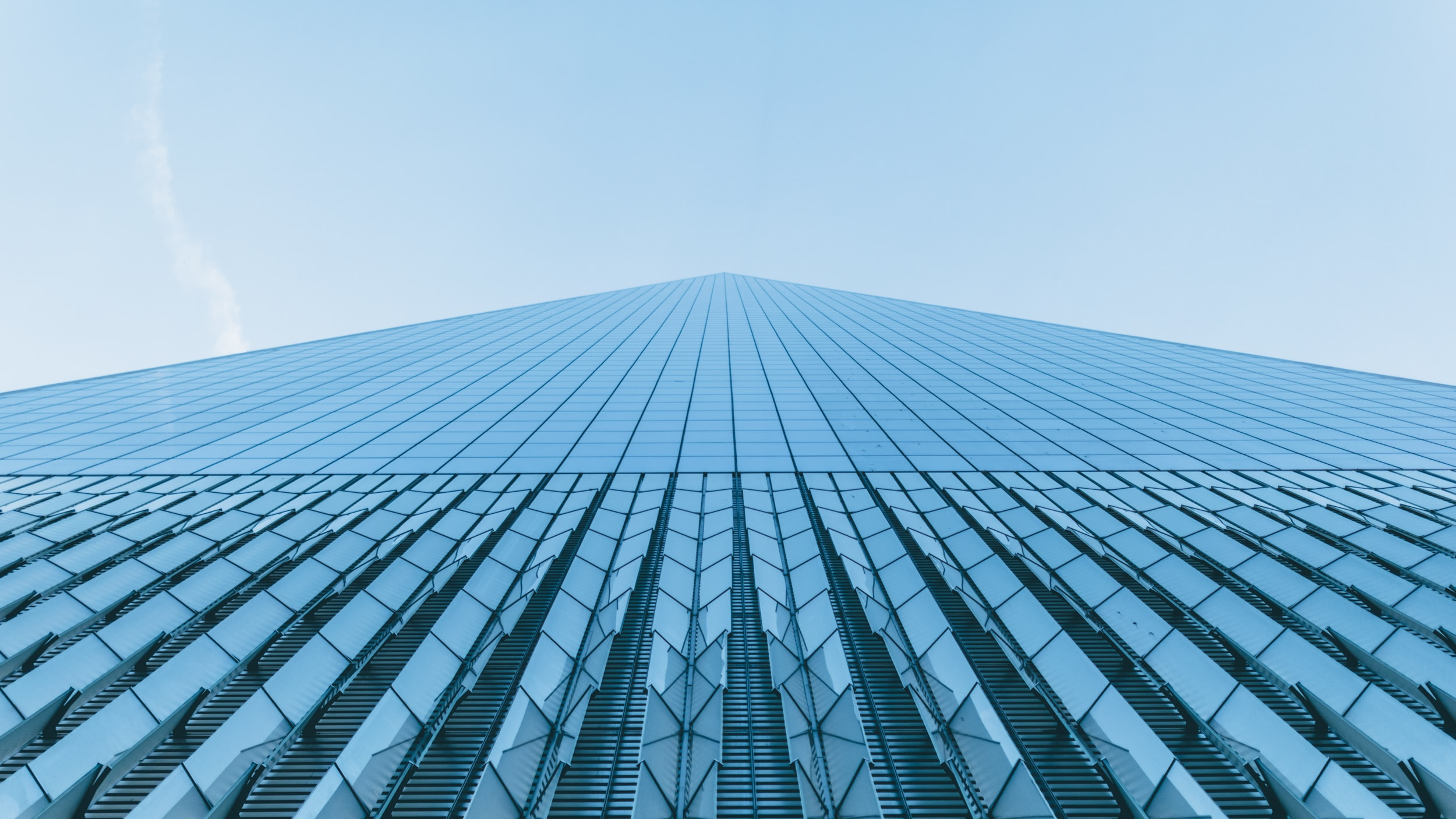 A low-angle shot of a towering skyscraper with a glass facade