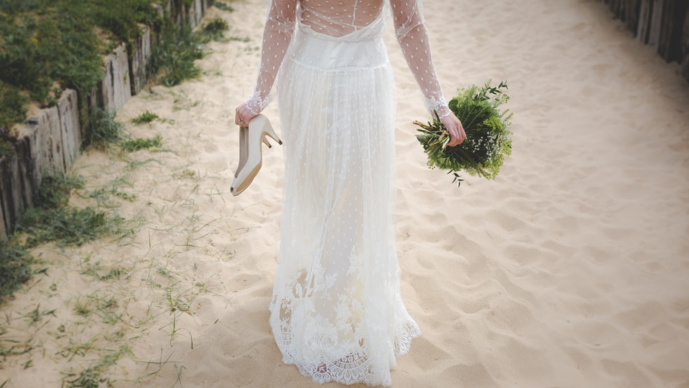 woman wearing white wedding dress walking on white sand holding pair of beige shoes and bouquet of flowers during day