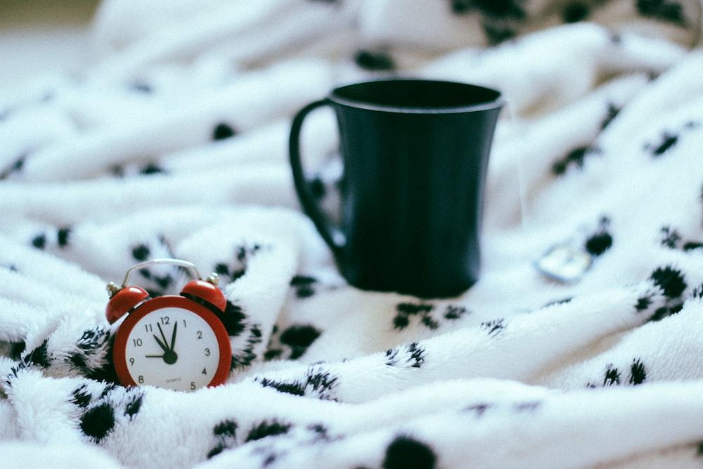 green ceramic mug near analog alarm clock