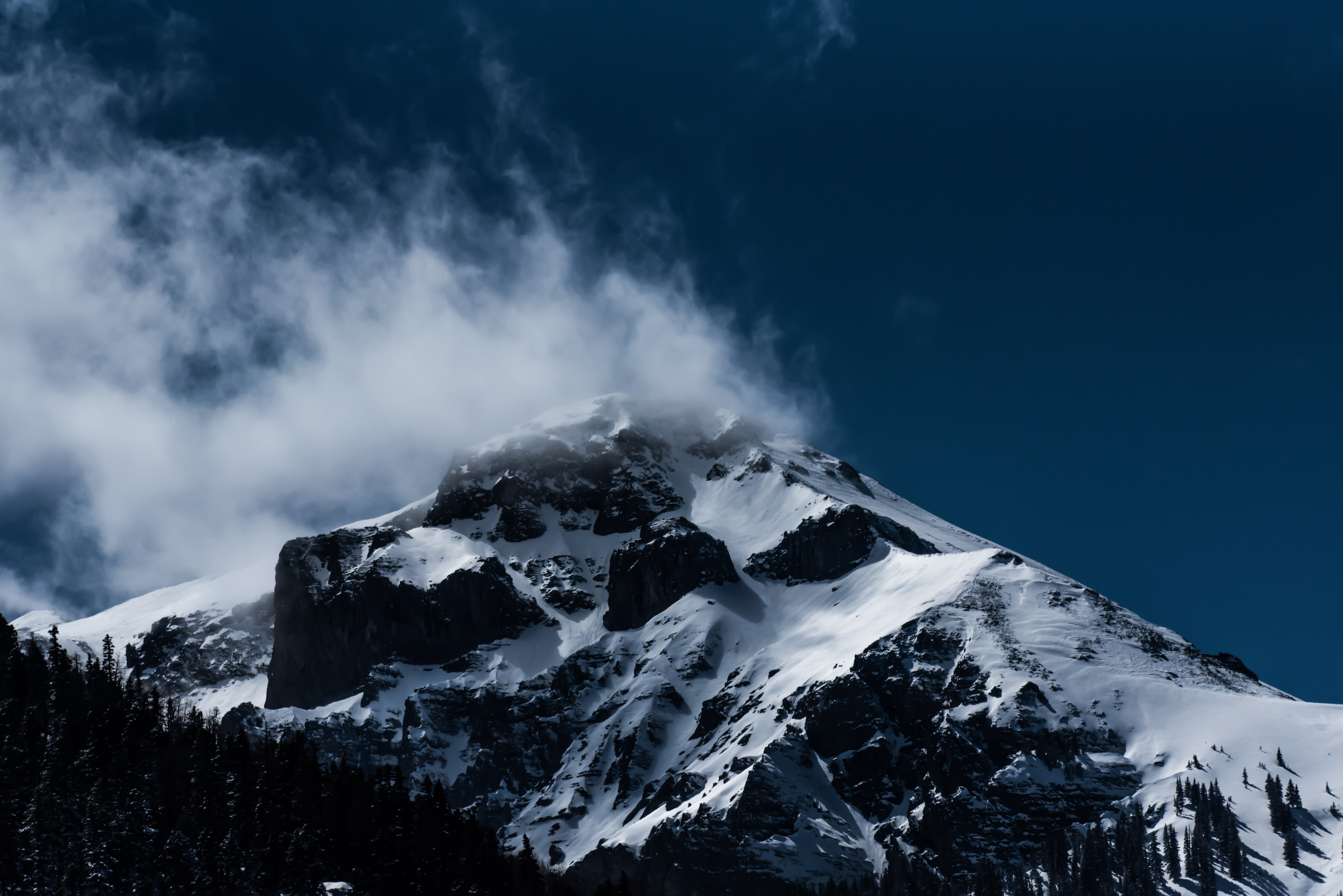 Wisps of smoke and clouds over a snowcapped mountain peak