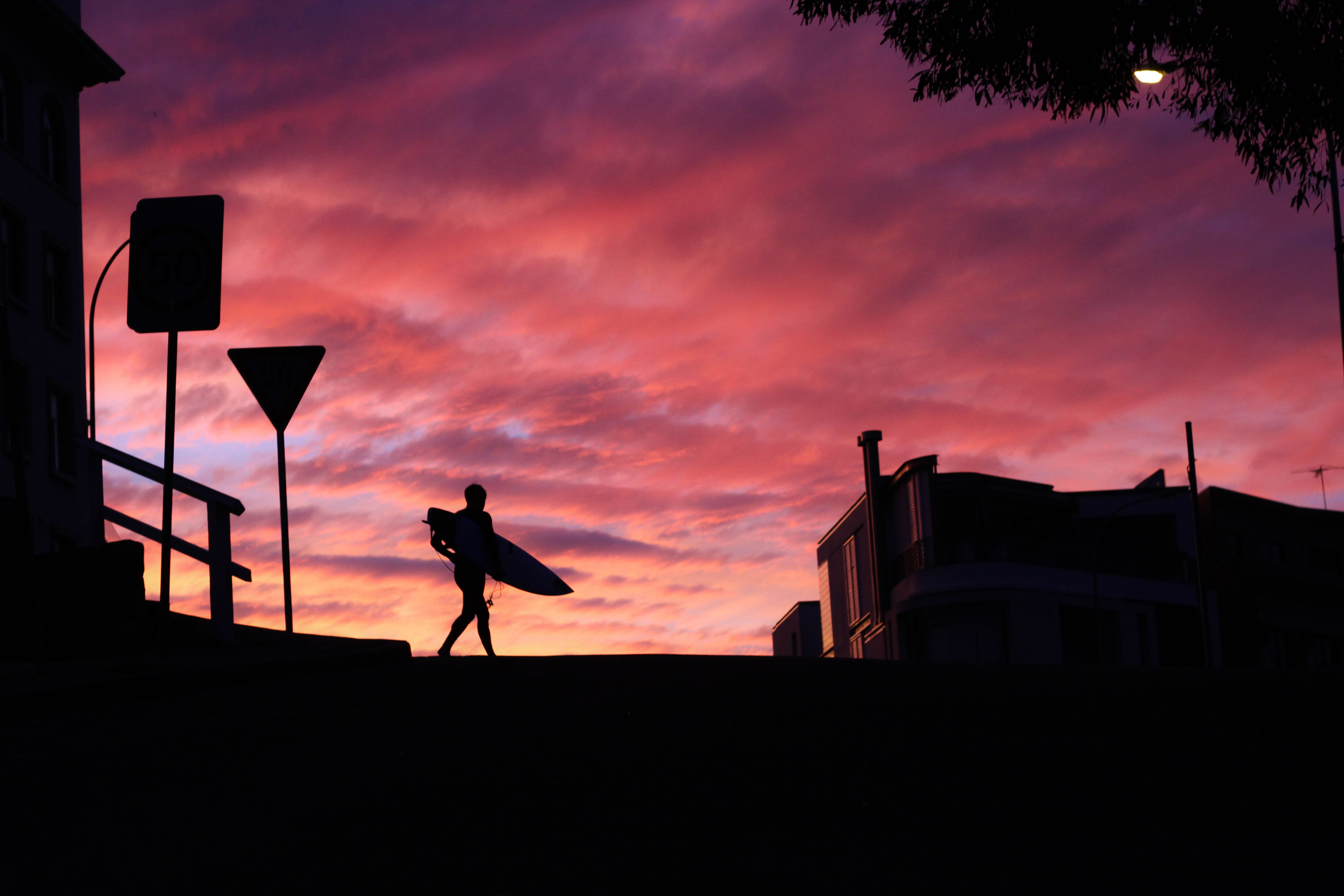 Surfer silhouette crossing the street at Bondi Beach after sunset