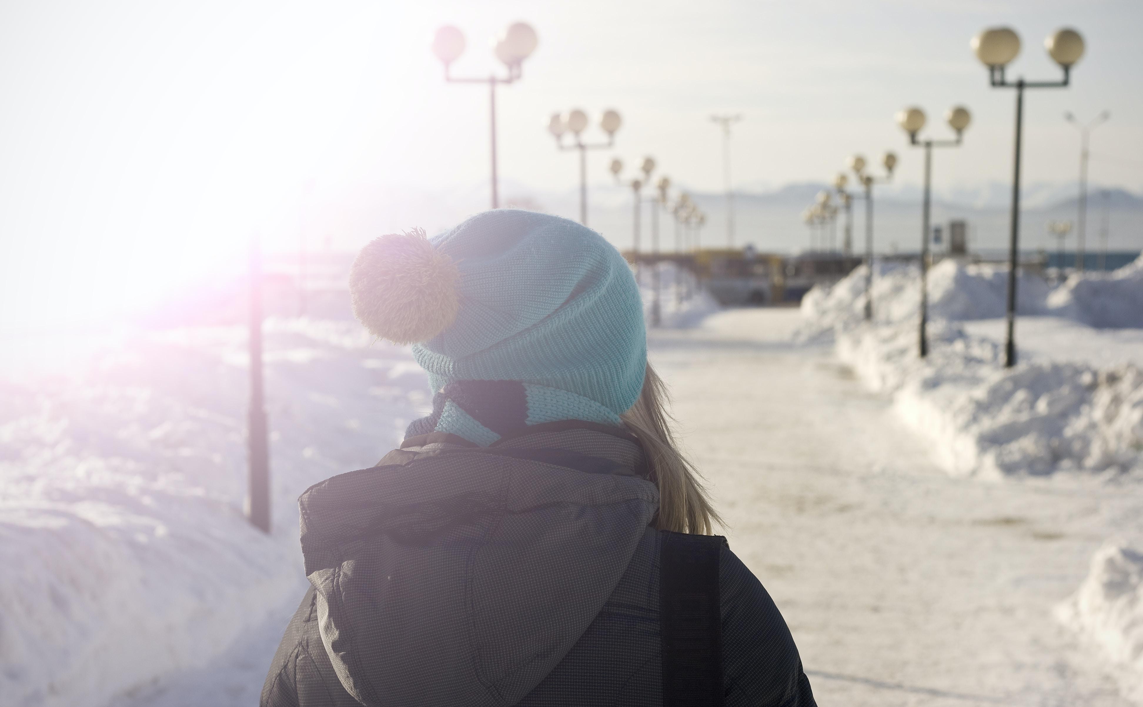 A female in a blue hat walking a snowy path of streetlights in the sun