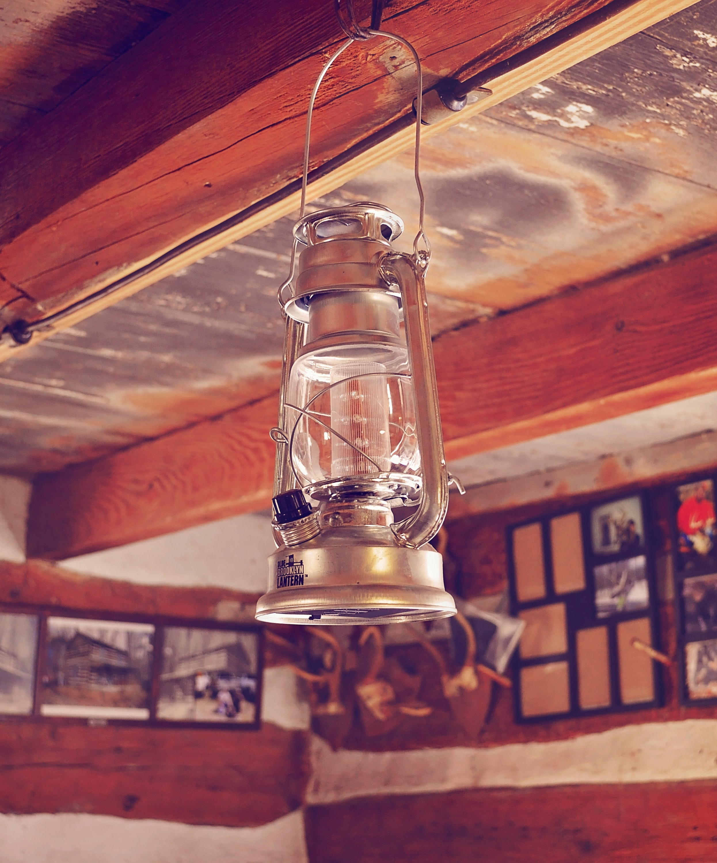 An old, rustic lantern hangs in a wooden lodge with photos on the walls