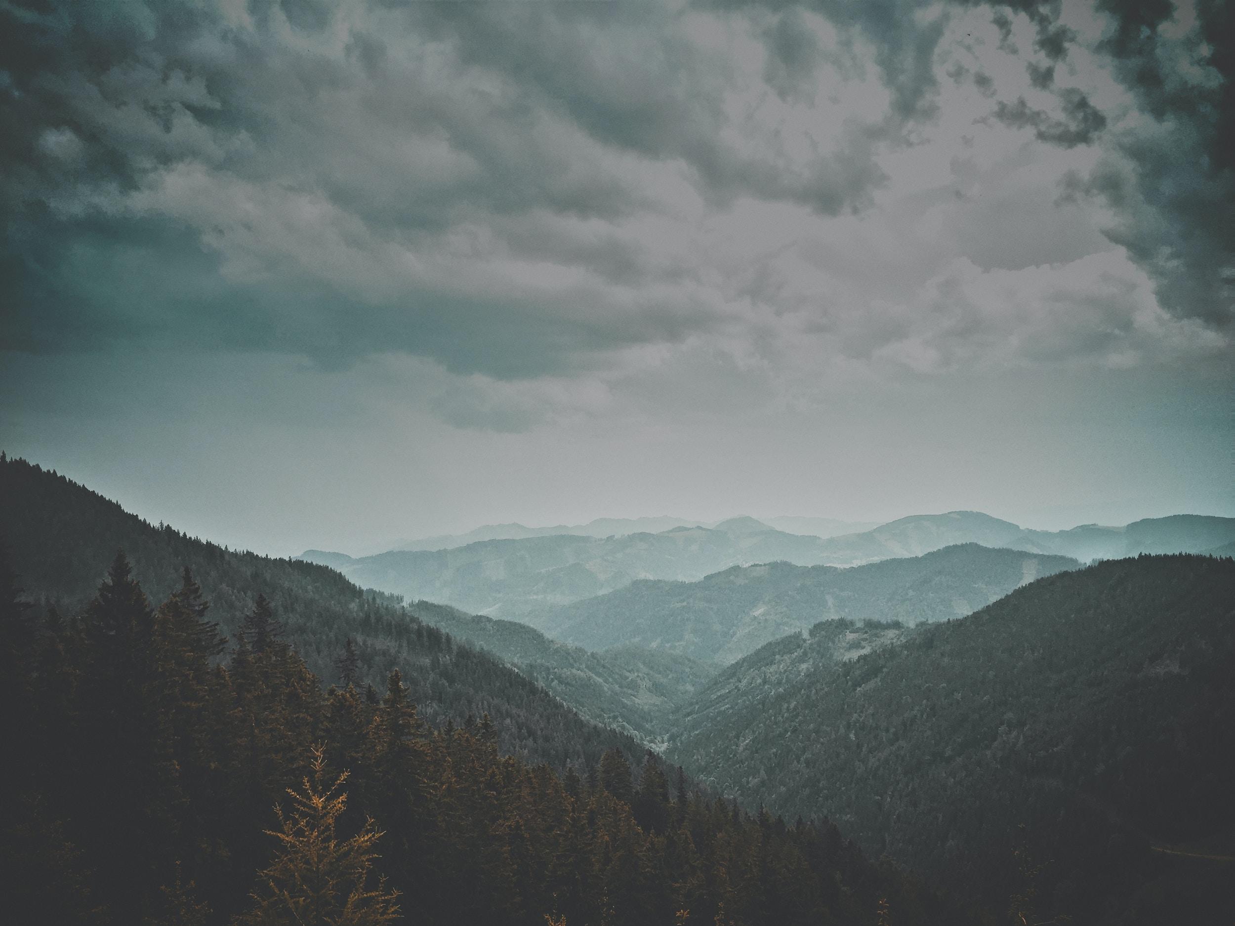 A mountainous landscape in fog under heavy clouds