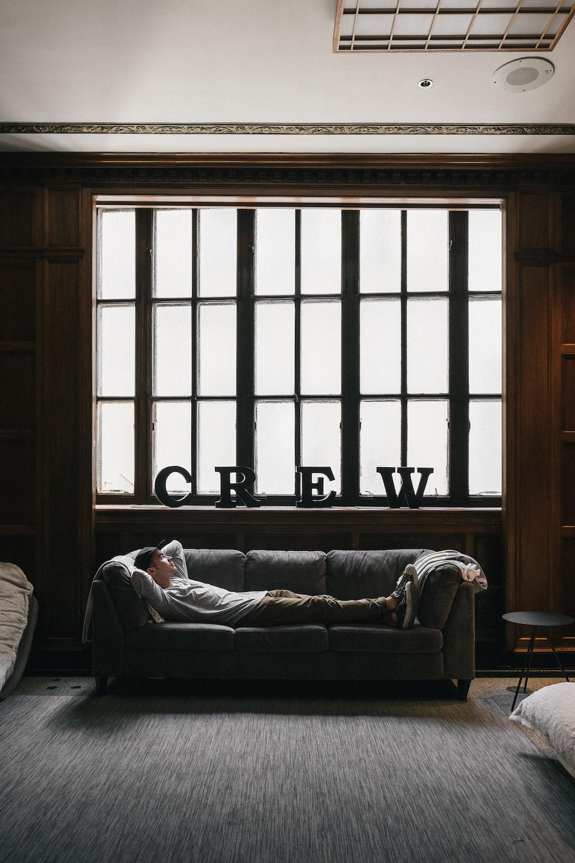 photo of person laying on sofa near window
