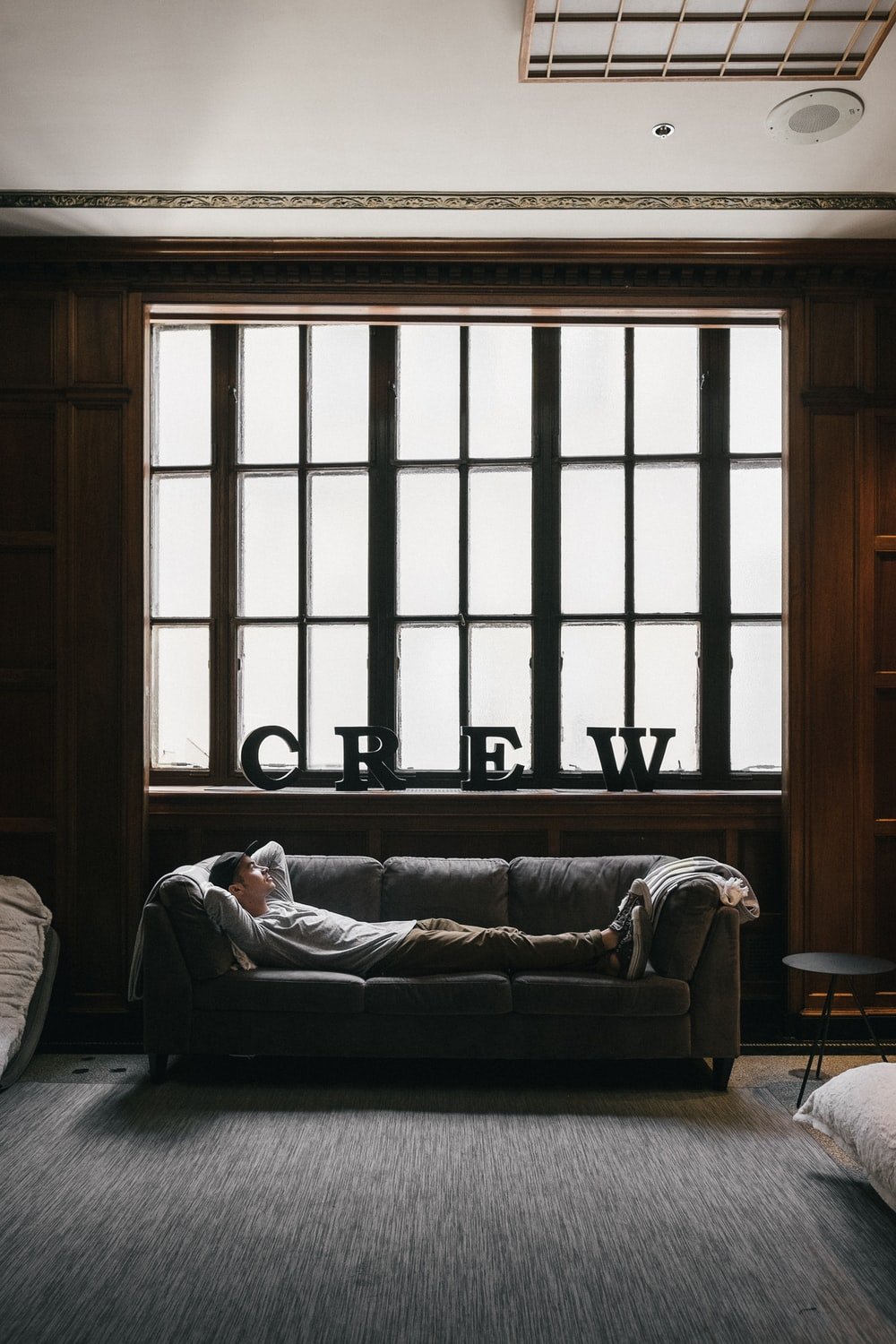 photo of person laying on sofa near window