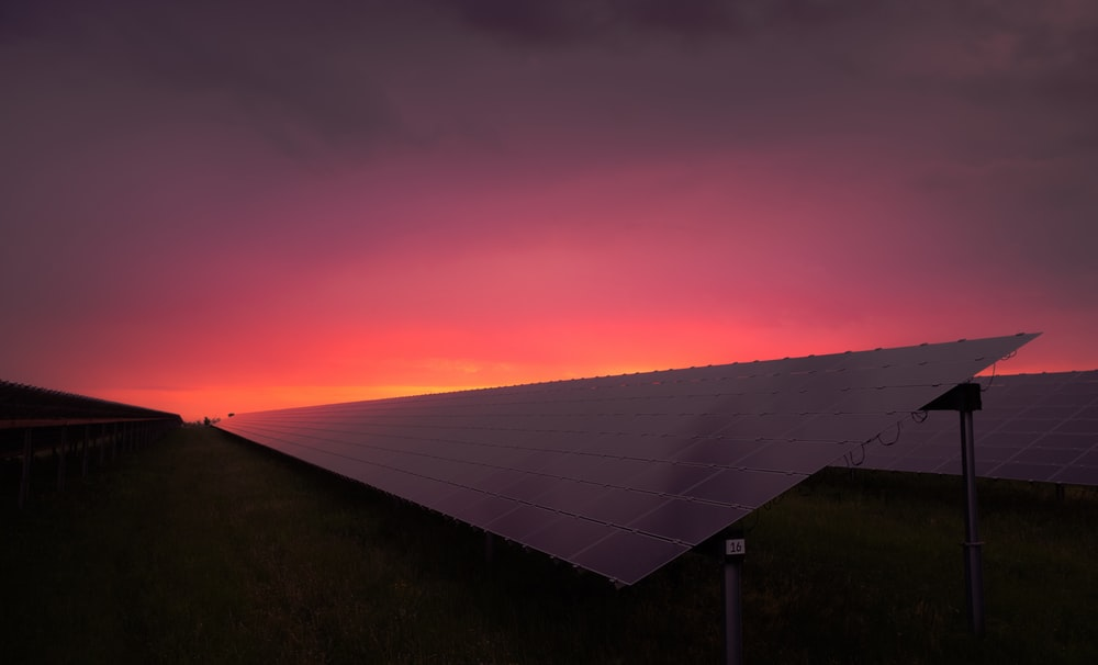black solar panel under red and gray clouds