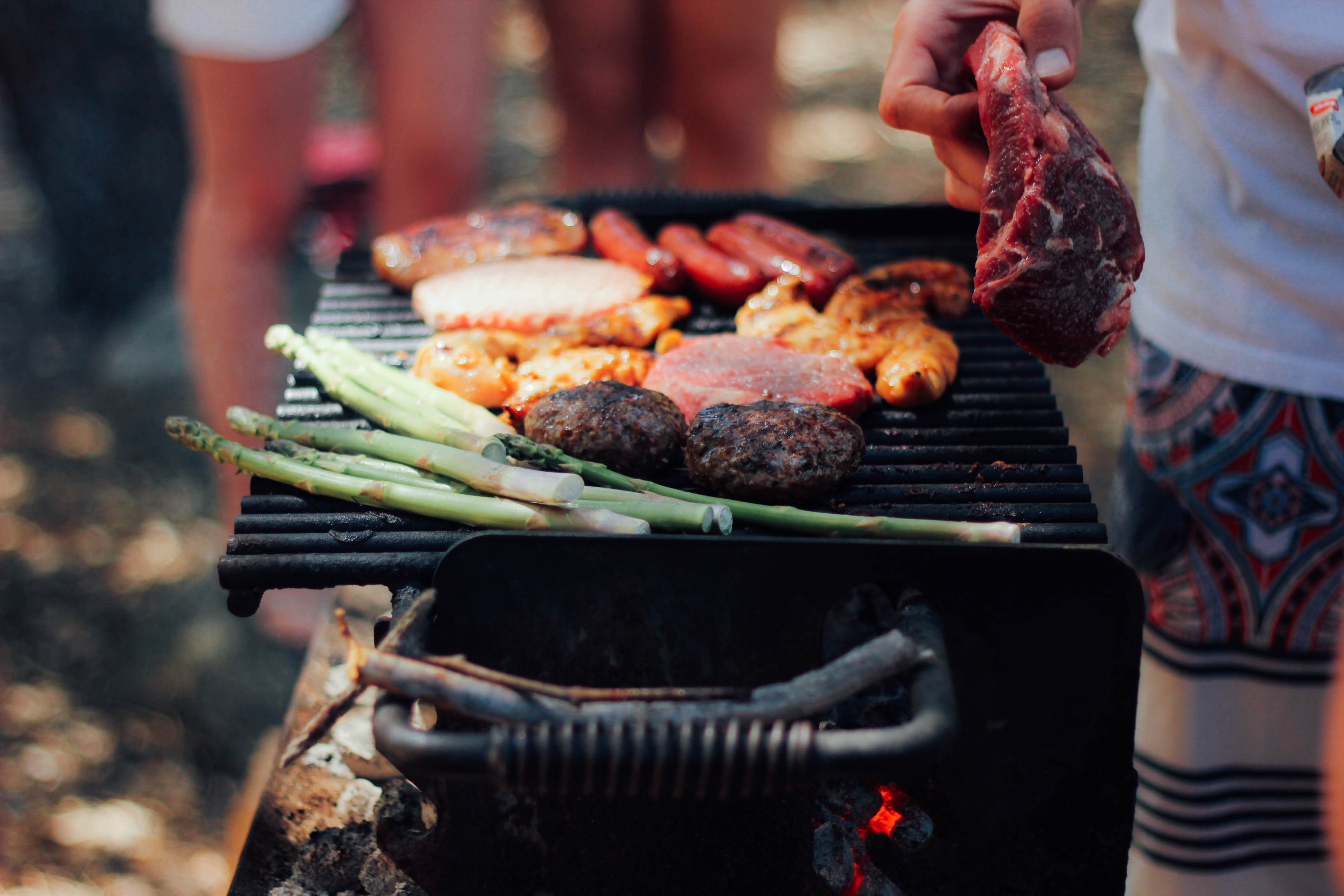 A charcoal grill with meat, burgers, hot dogs, and asparagus at a BBQ
