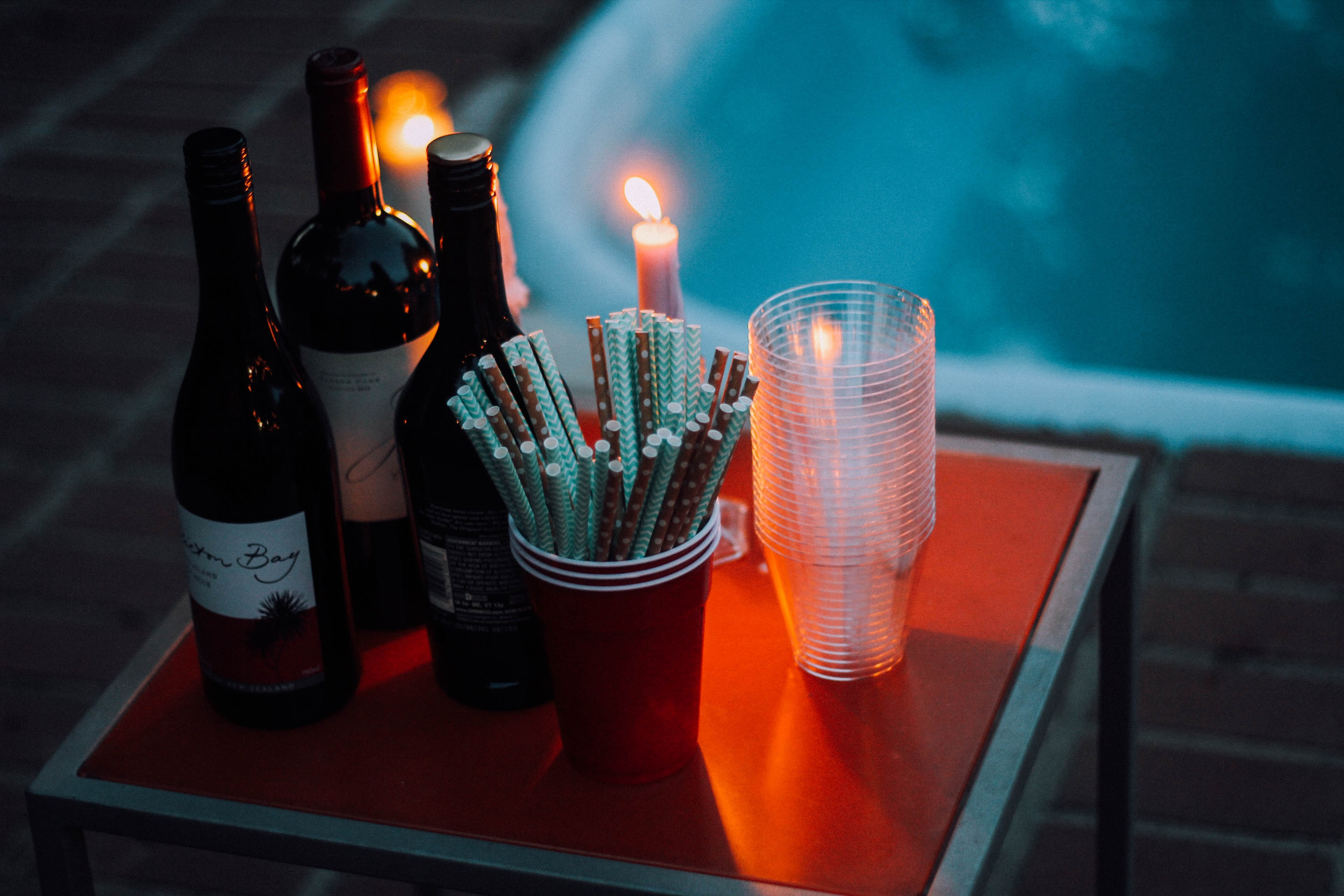 A tabletop containing wine, straws, candles with flames and plastic cups by a pool in redding