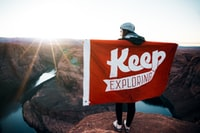 person with banner standing on cliff