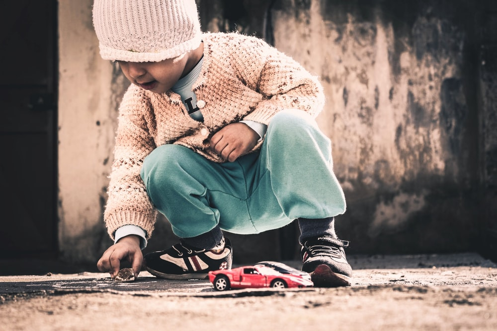 child squatting on beige floor holding rock near red sports coupe scale model at daytime