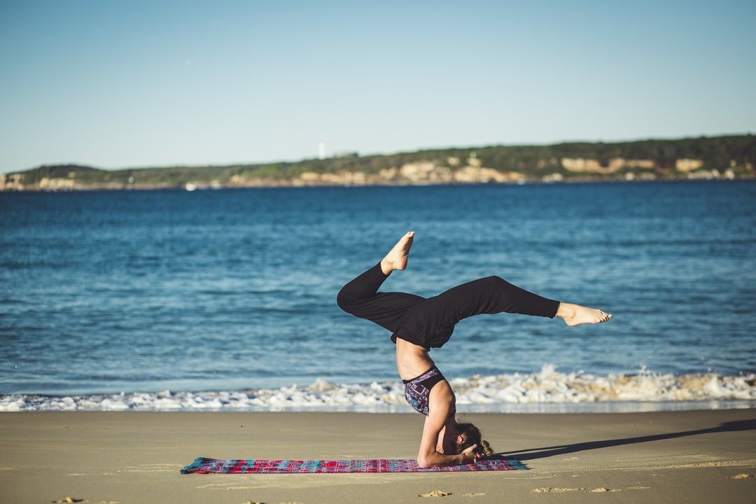 A woman doing yoga on a pink and blue yoga mat by the ocean
