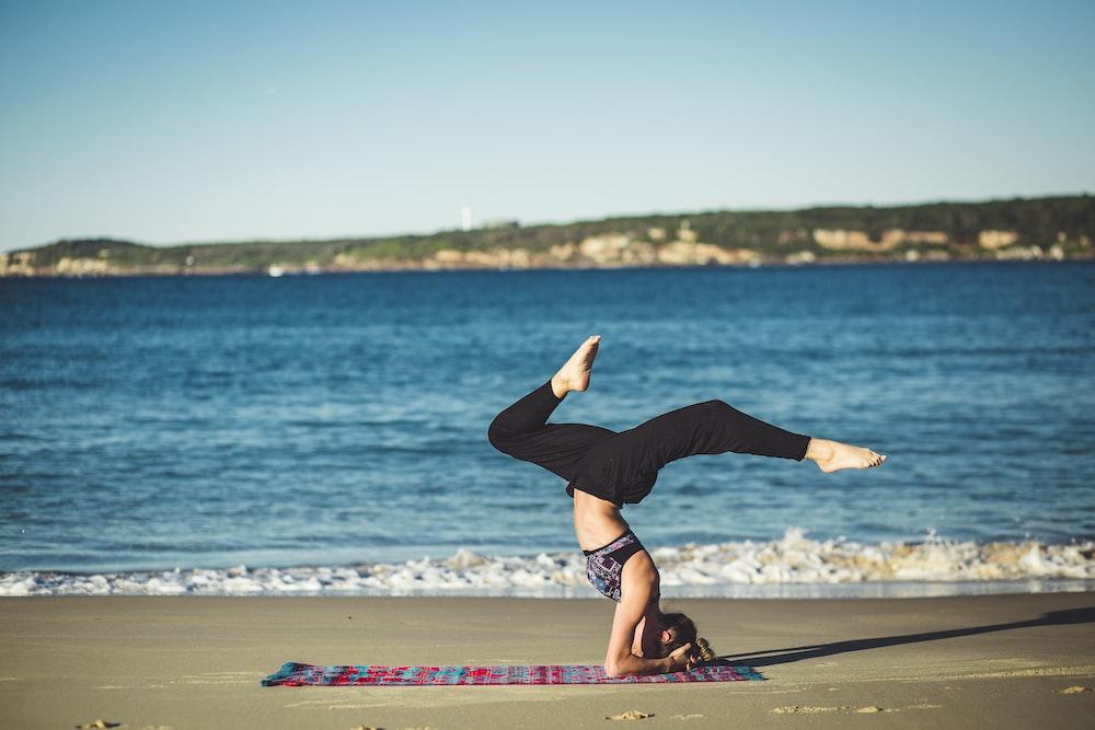 woman doing yoga beside the seashore