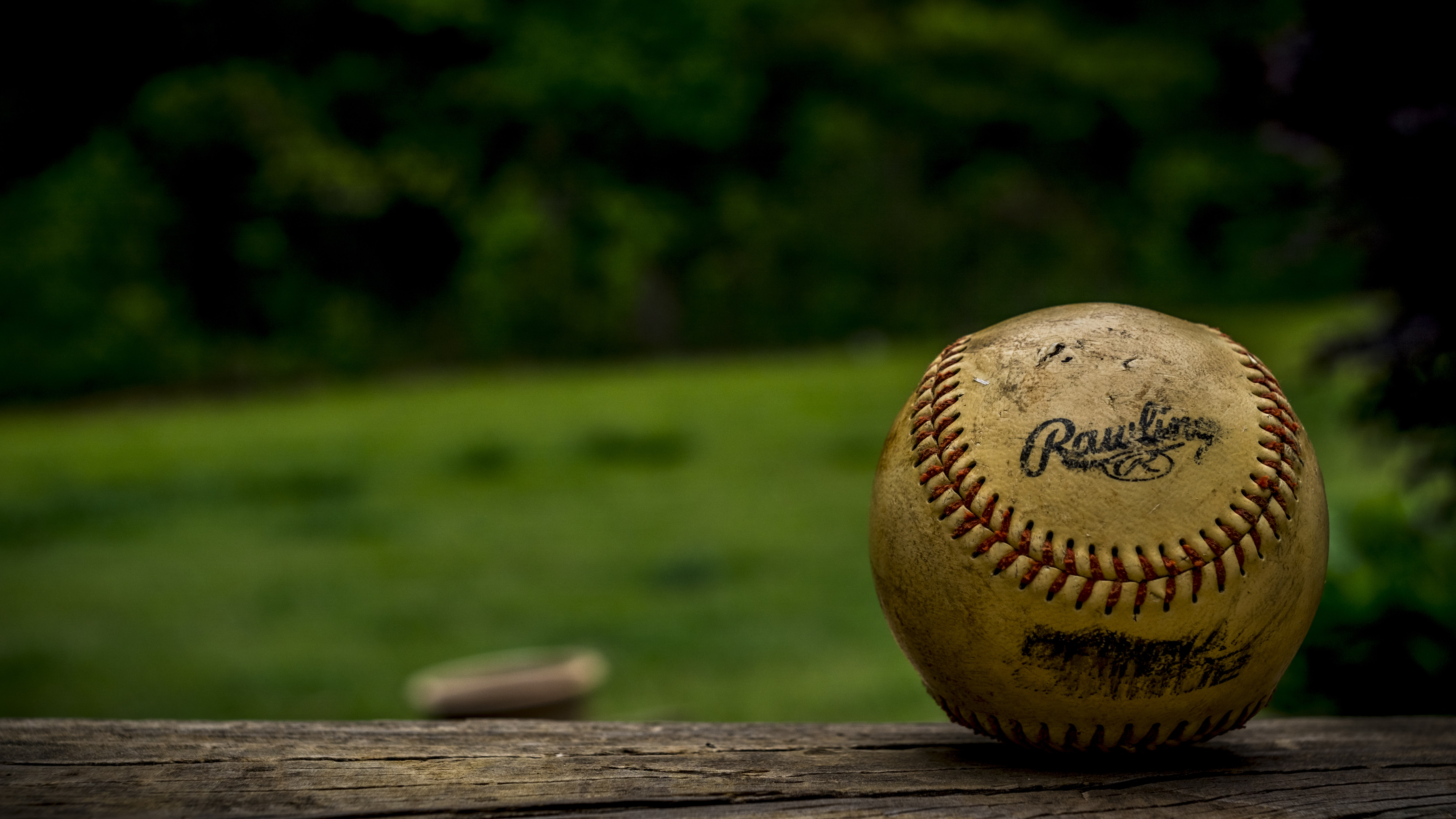 The macro view of an old baseball on a wood surface