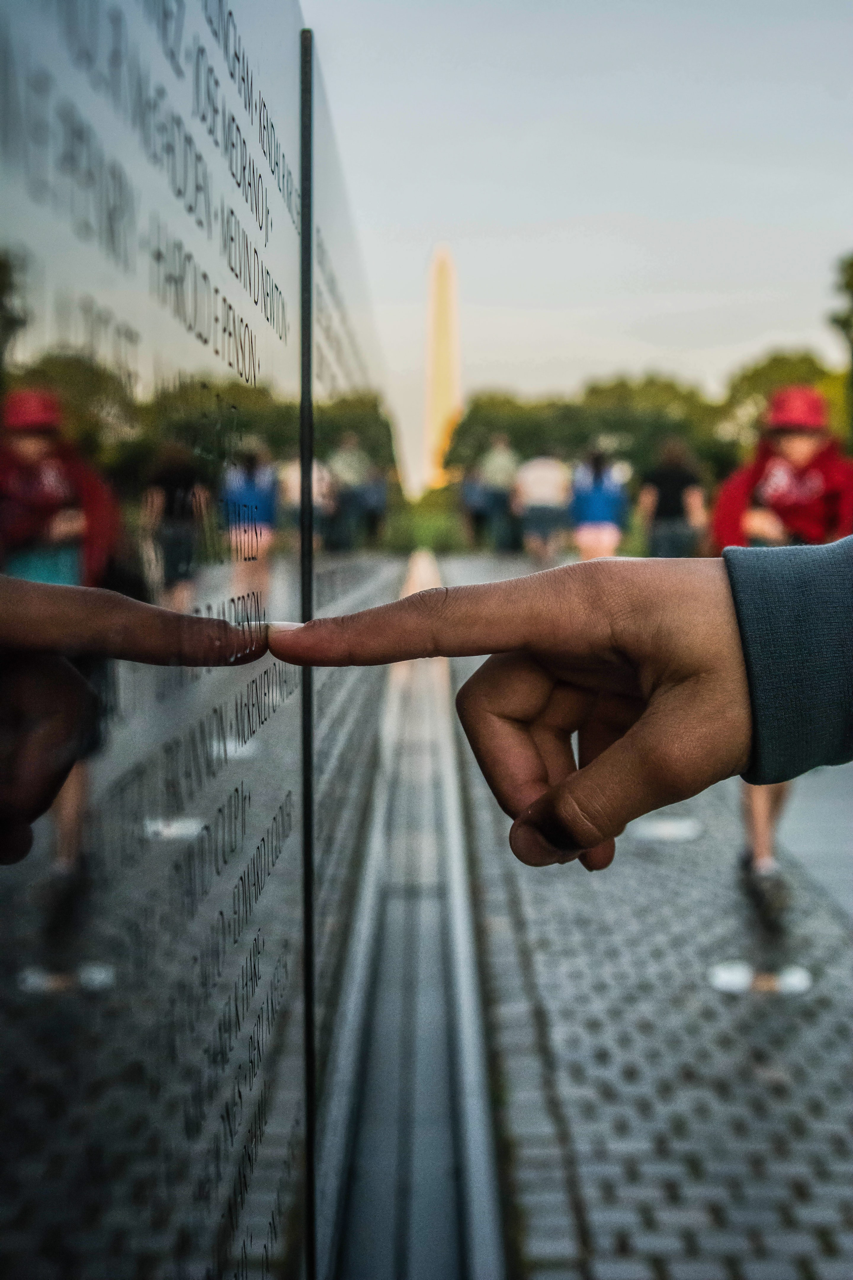 A person pointing at a monument on Memorial Day.