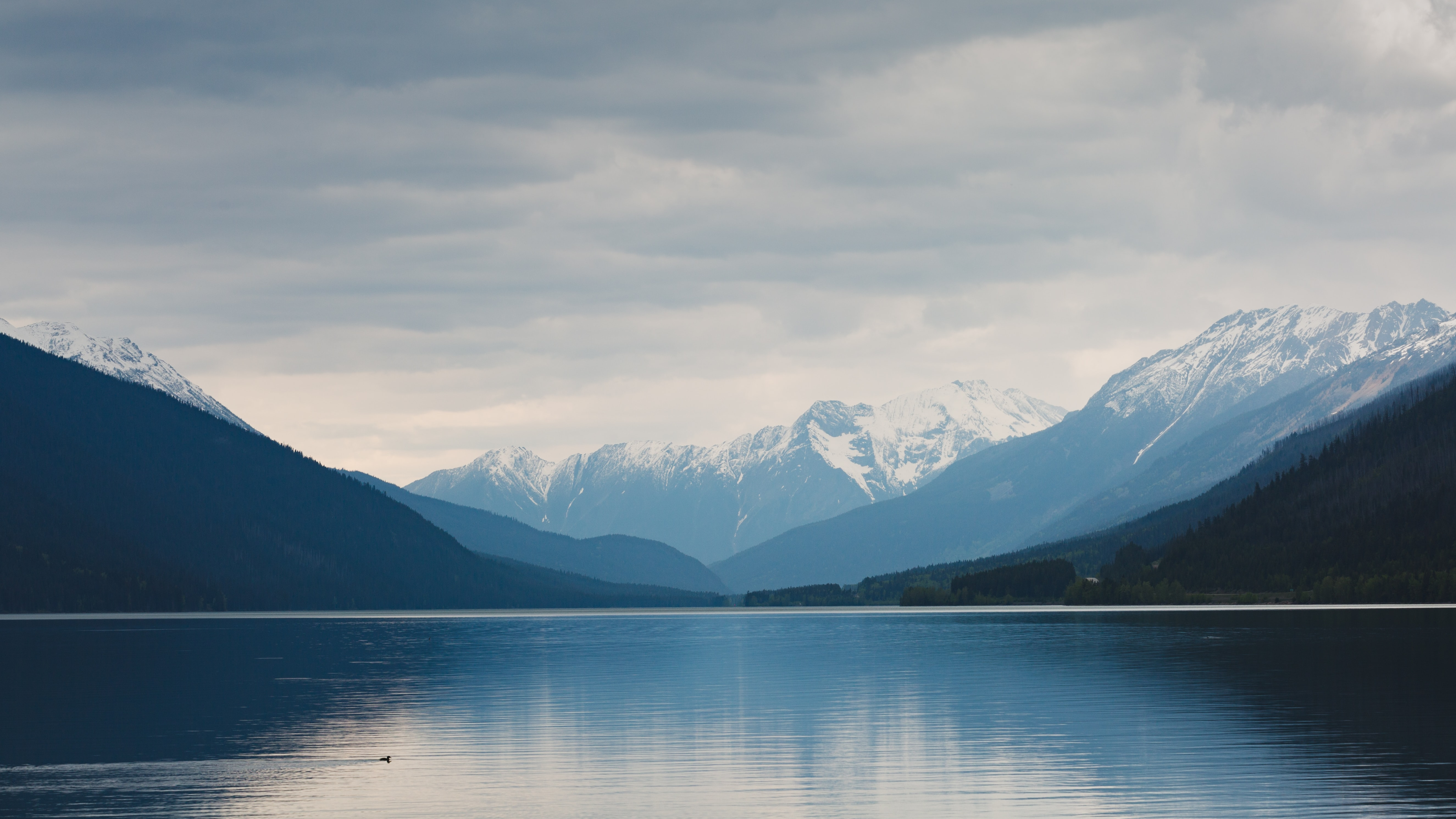 A landscape view of snow covered mountains next to calm blue water in cloudy weather.