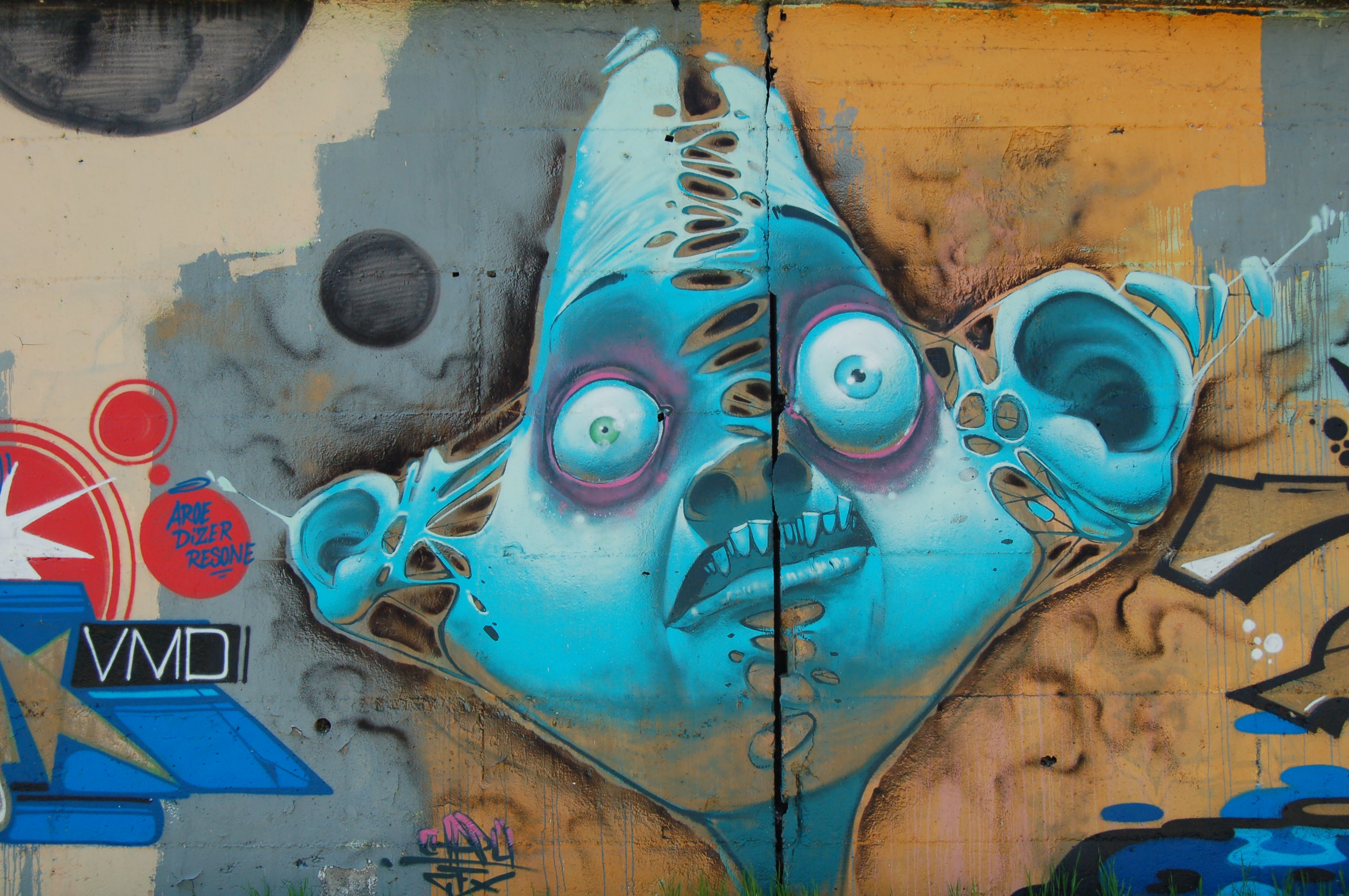 A funny looking monster character drawn with spray paint on a building wall.