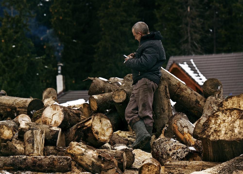 man in black jacket and brown pants sitting on brown log during daytime