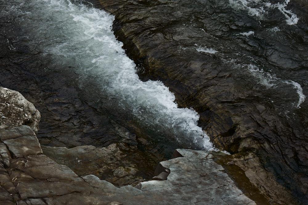 bird's eye view of water crashing boulders