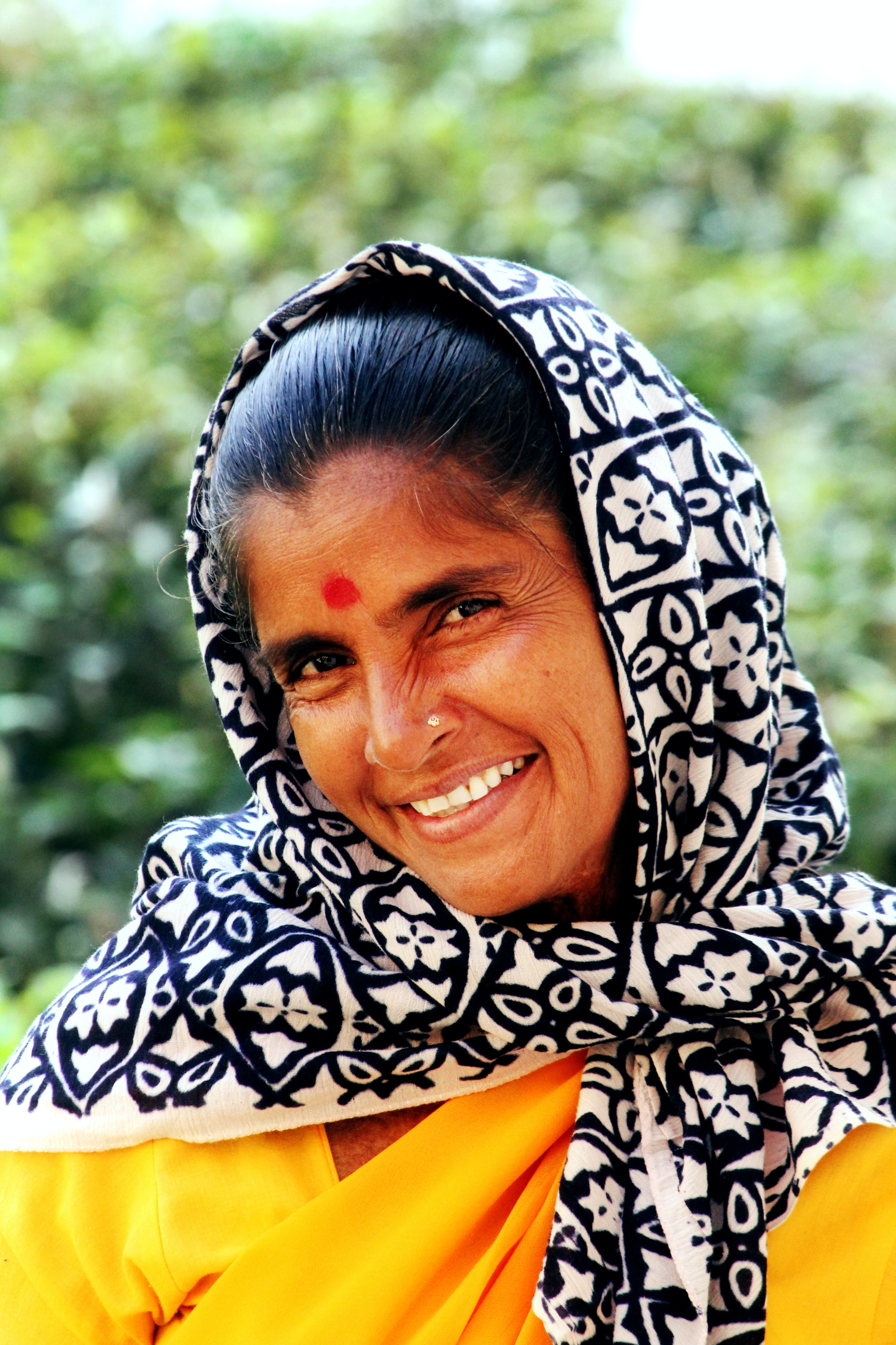 A woman with black hair, a loose head scarf, and yellow top smiles. She has a bindi on her forehead and a small piercing in her nostril.
