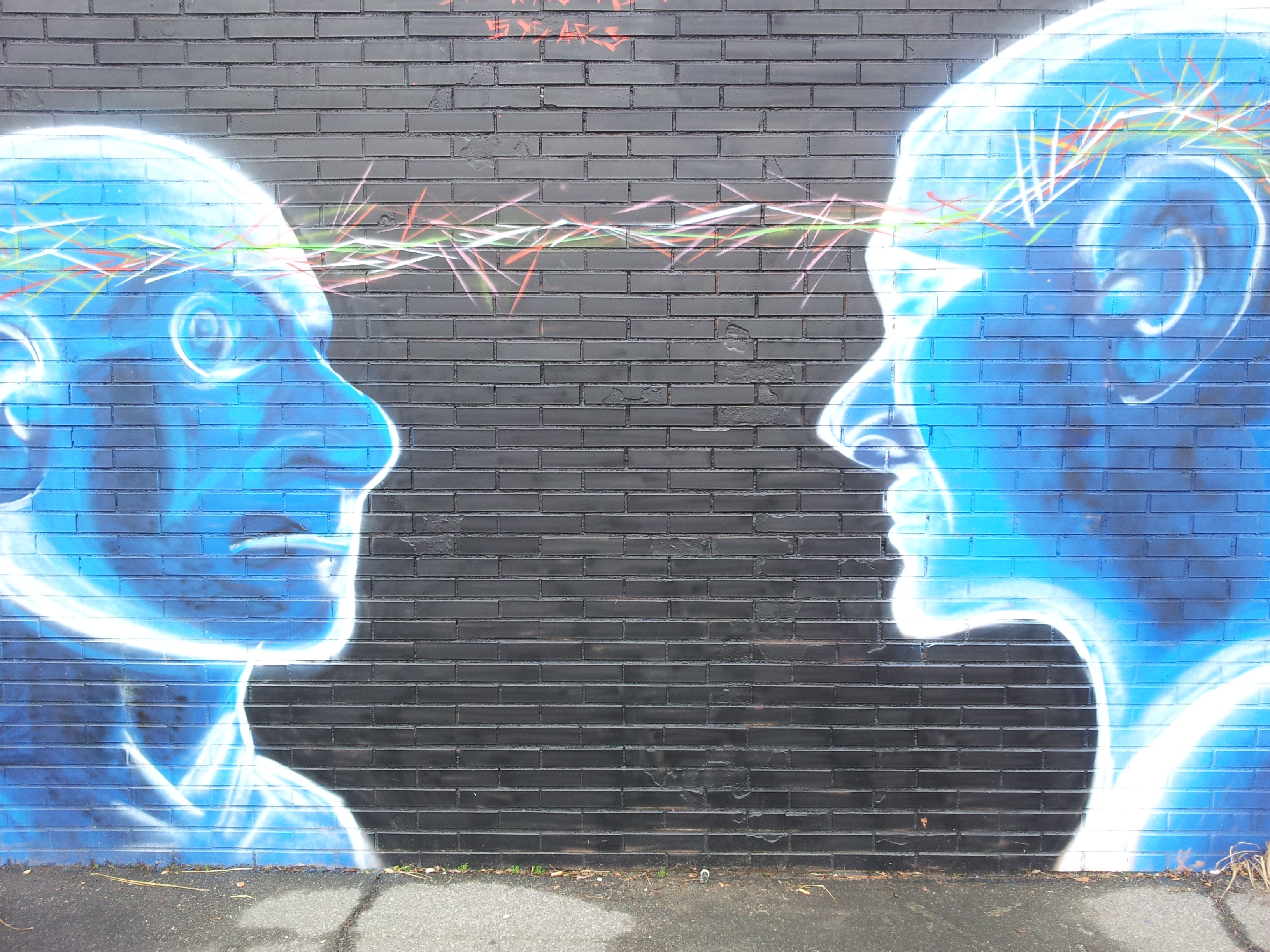 A brick wall mural of two cartoonish people staring at each other.