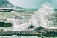 body of water splashing on gray rocks during daytime