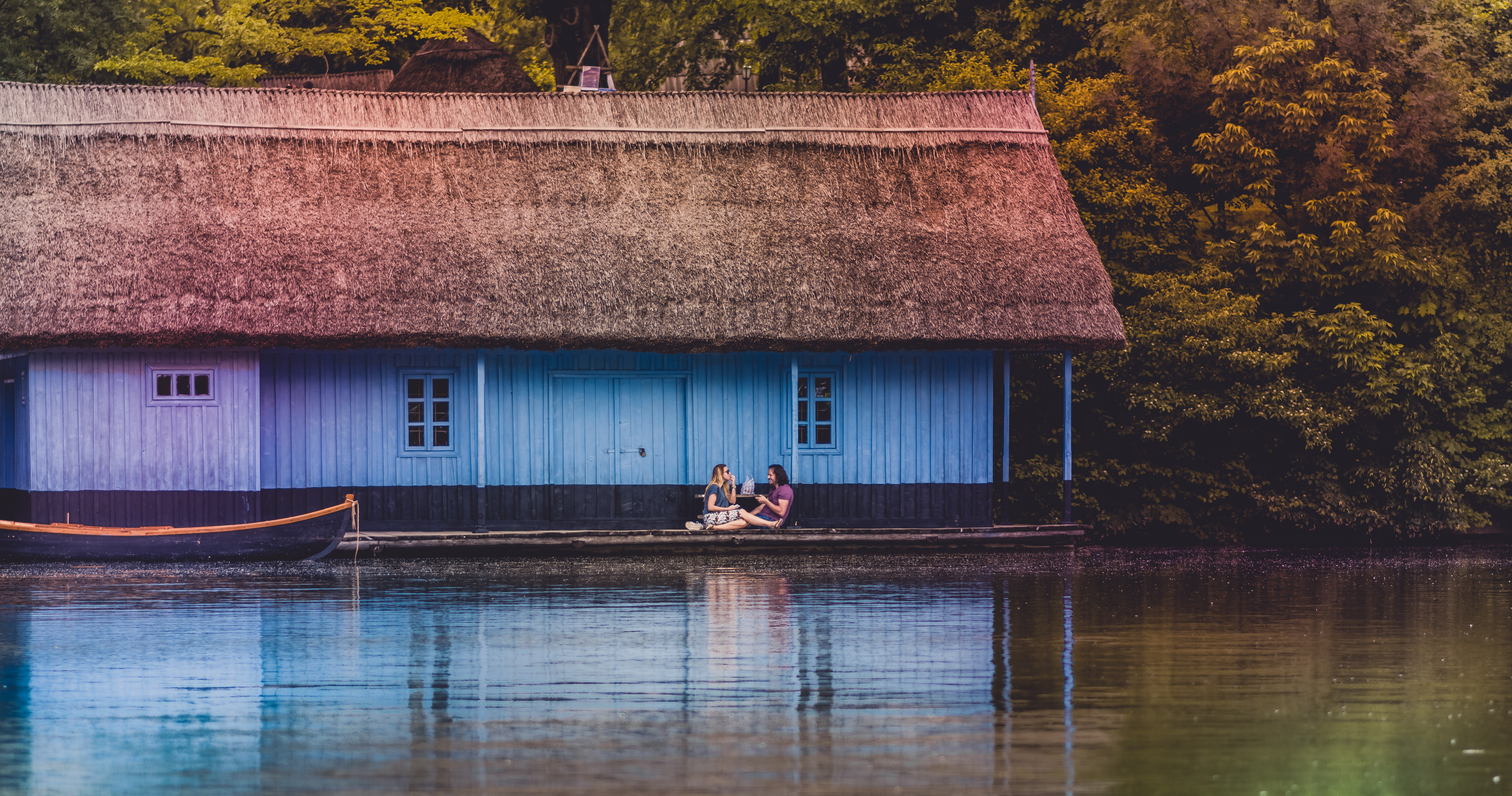 two person sitting on bench near body of water