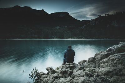 a man sits on a rock staring across a lake at dusk sadness zoom background
