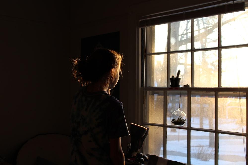 woman in room facing window