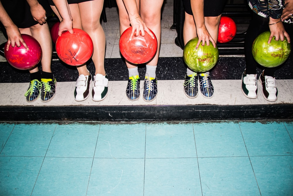 person holding bowling balls
