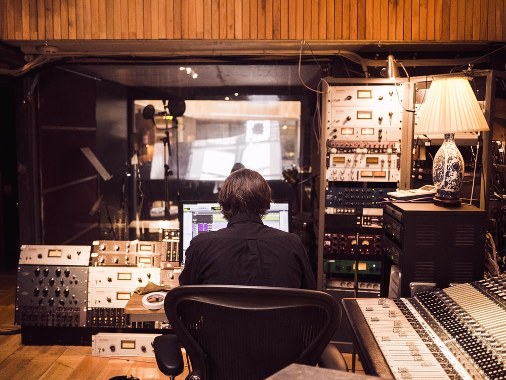 man in front of studio mixer and receiver