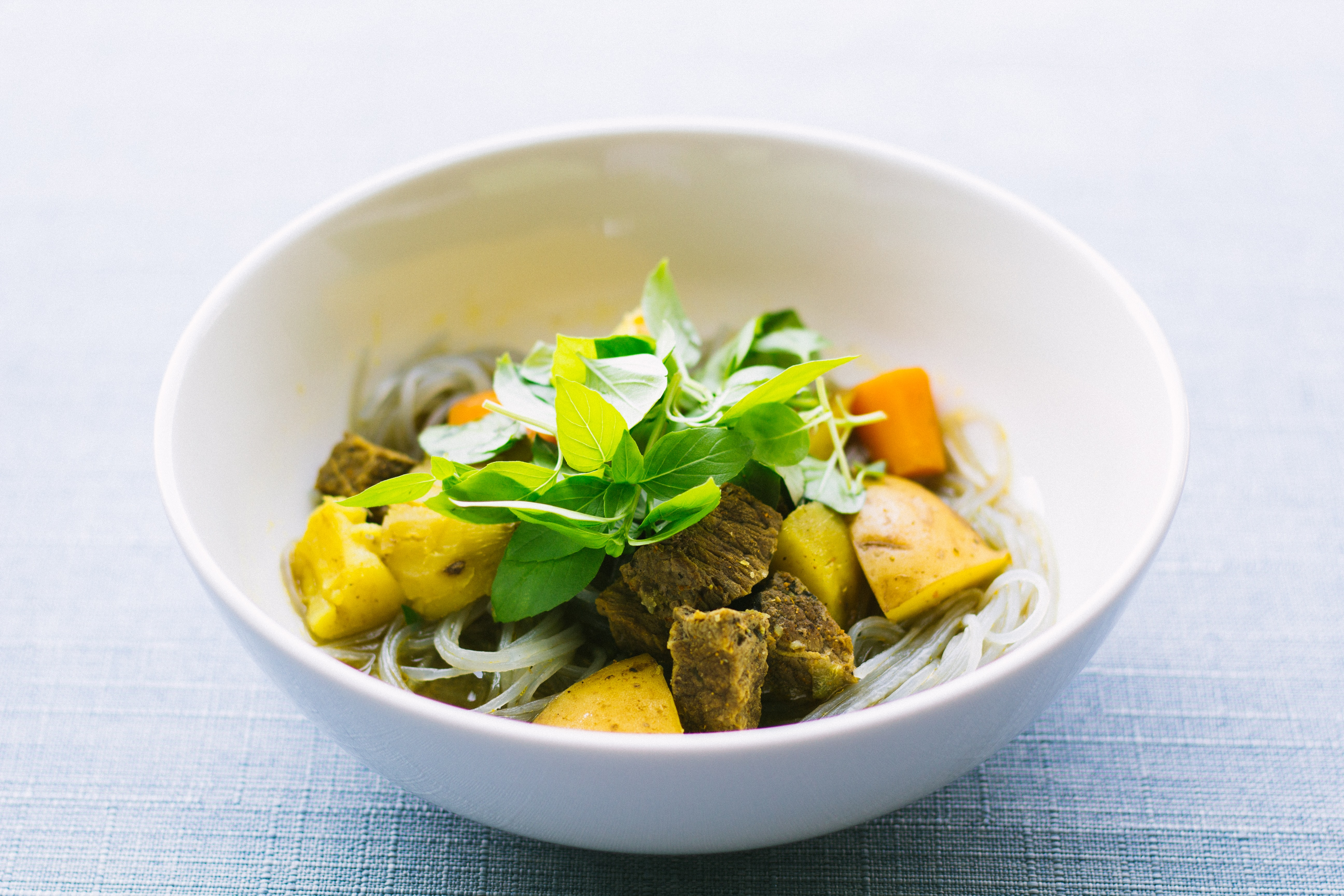 round white ceramic bowl with sliced meat and vegetable on gray surface