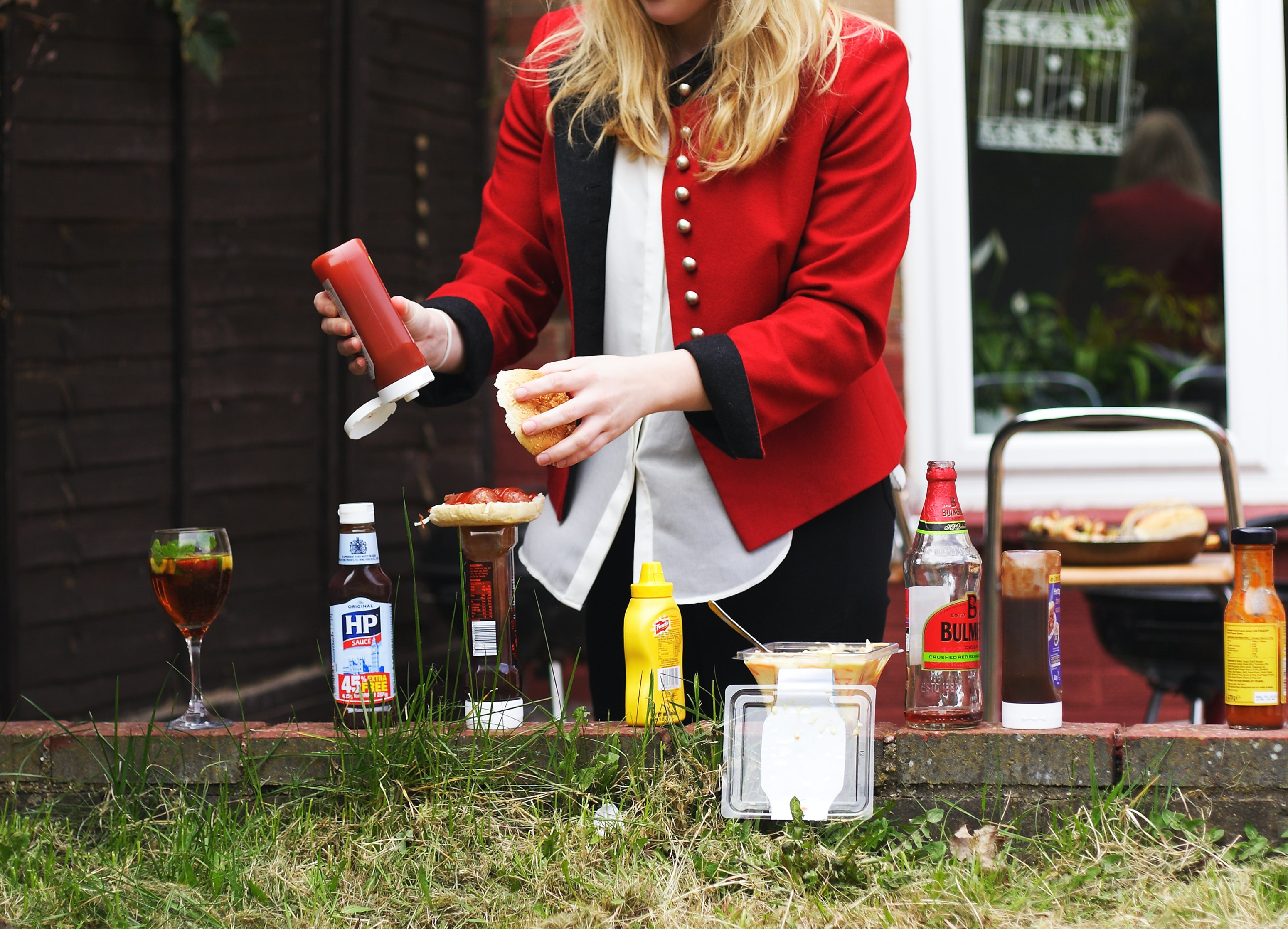 Woman in a red jacket putting ketchup on a hamburger