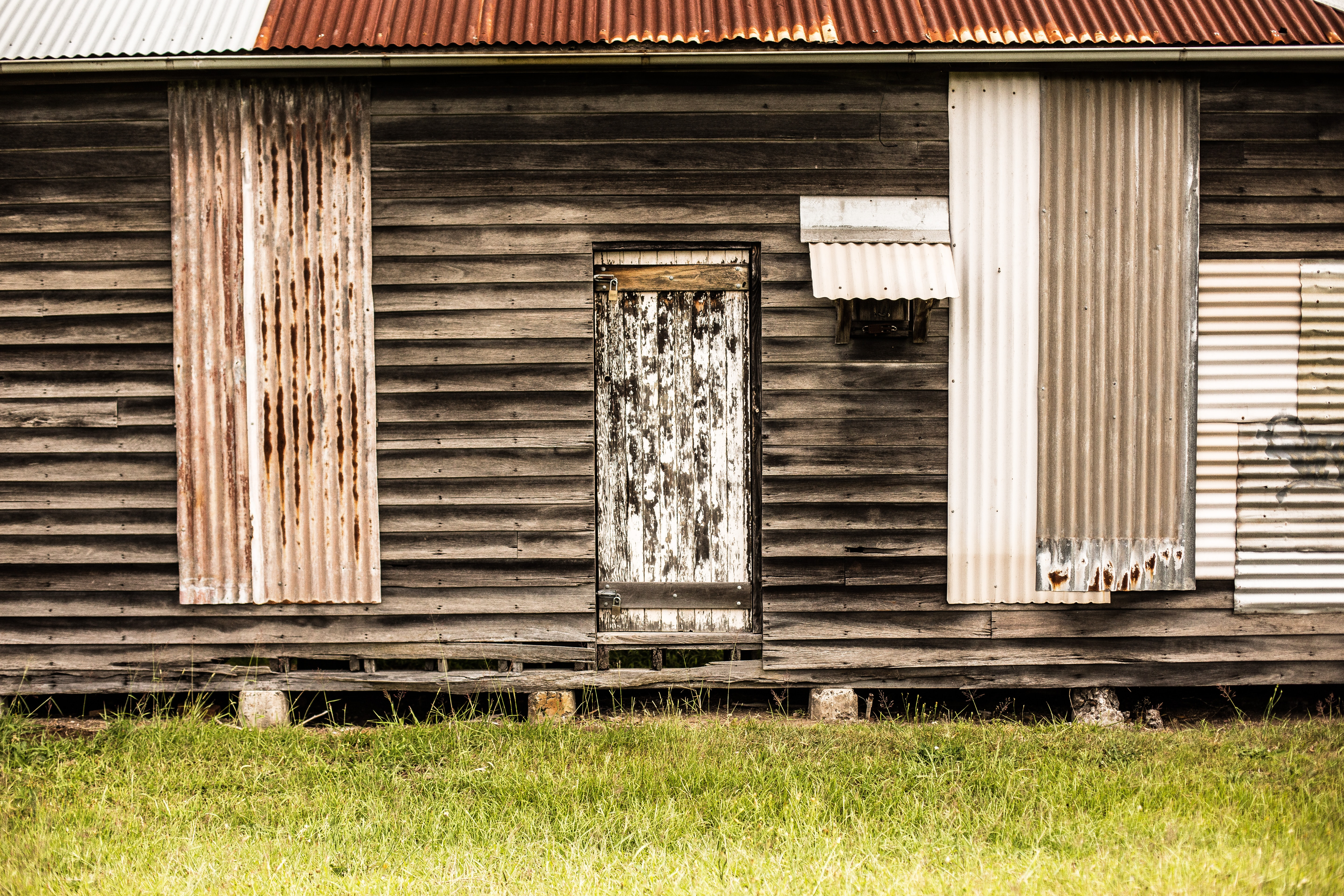 Wooden cabin with tin sheet patches and a decaying door in a grassy lawn