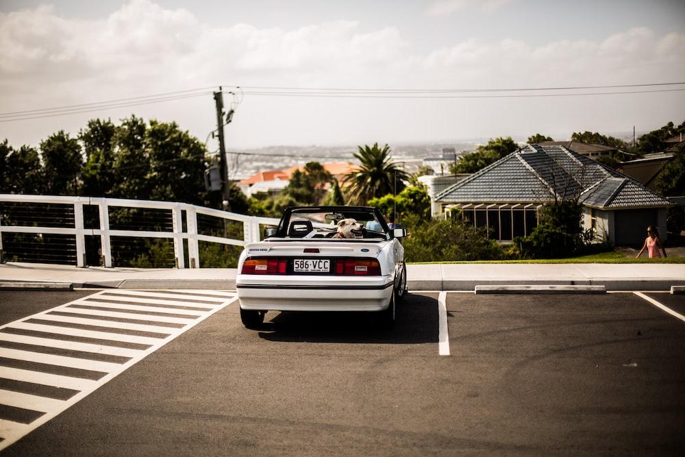 white convertible beside pedestrian lane