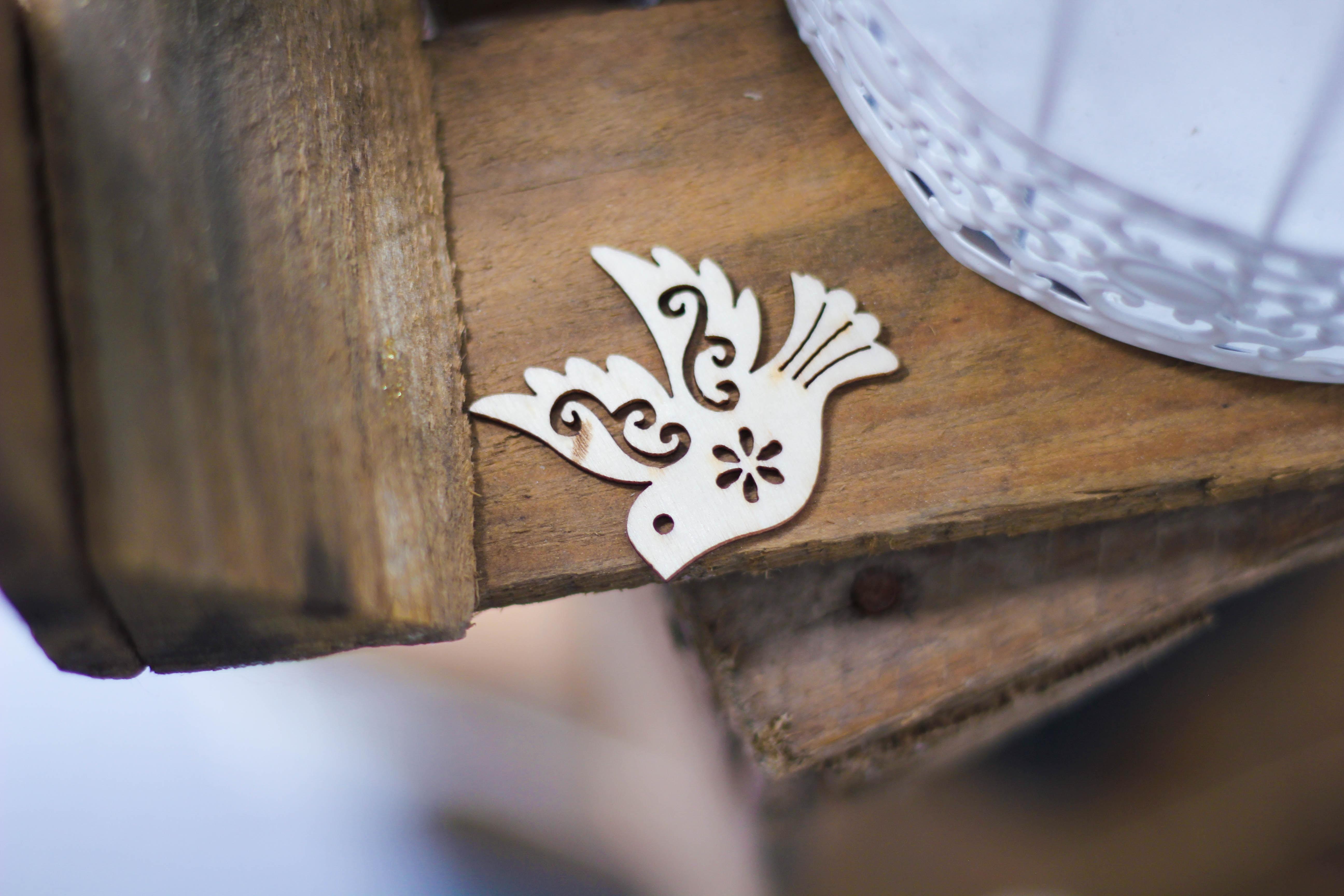 gray bird cutout decor on brown plank